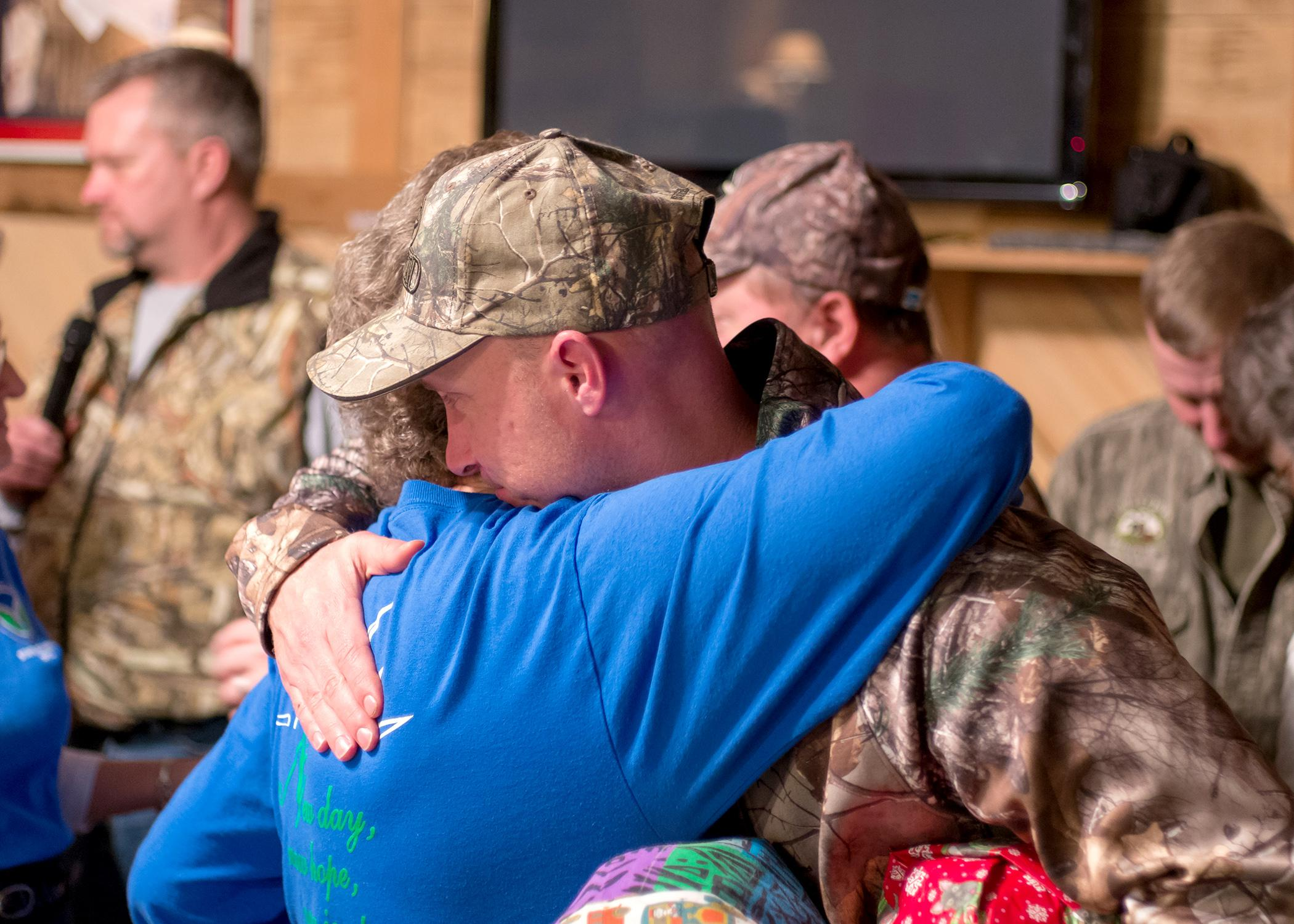 Wanda Hall of Mt. Olive hugs Paul O'Neill of Memphis, Tennessee, a veteran of the U.S. Army's 3rd Stryker Brigade on Dec. 12, 2014, in appreciation for his military service. O'Neill is one of nine soldiers who participated in the Hot Coffee Hunts for Heroes and received quilts from the Mississippi Homemaker Volunteers of Covington County. (Photo by Robert Lewis)