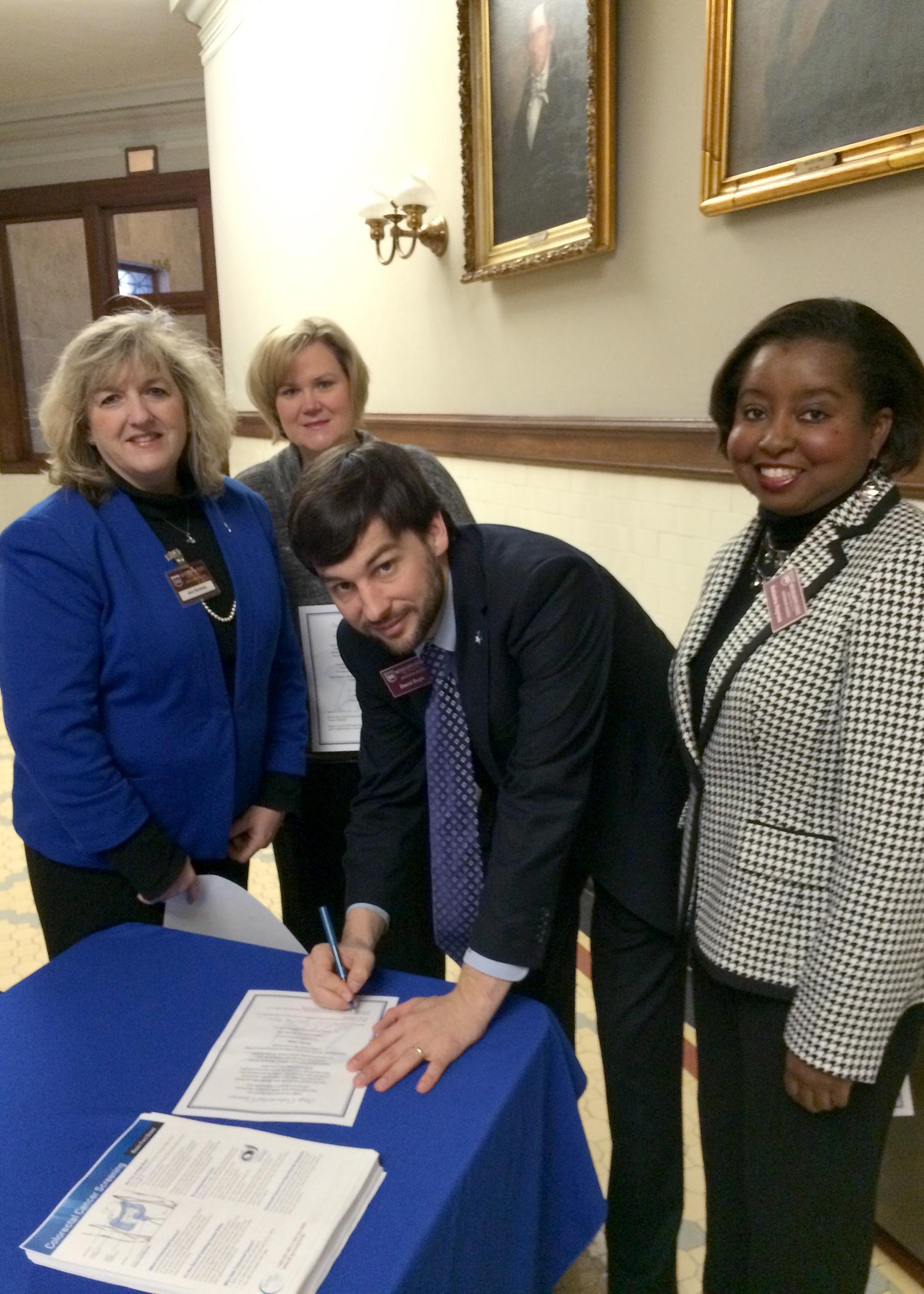 Mississippi State University Extension Service health specialist David Buys signs a pledge to be screened for colorectal cancer in 2015. Other representatives of the MSU Extension Service, Ann Sansing (from left), Theresa Hand and Natasha Haynes, are joining him in the awareness event at the Mississippi Capitol on March 9, 2015. (Submitted photo)