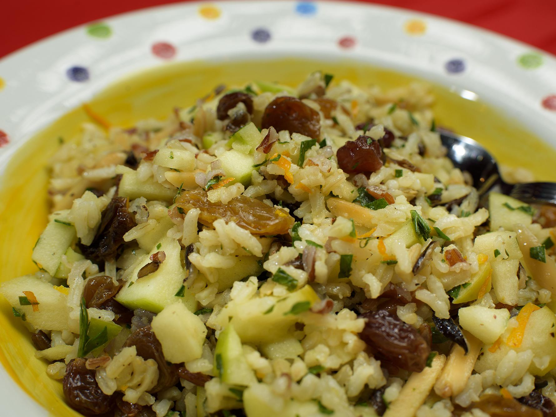 A mixture of rice, apples, raisins and almonds is displayed in a colorful bowl.