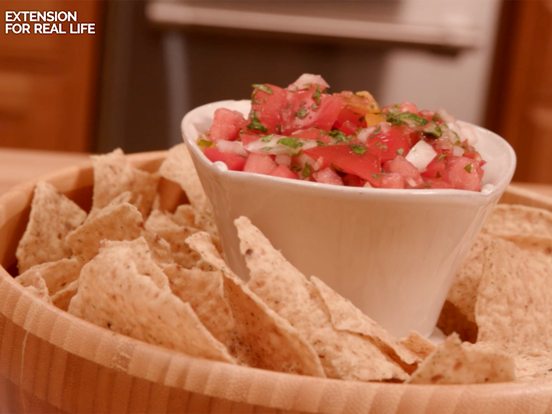 Homemade pico de gallo in a white container placed in the center of a wooden bowl of tortilla chips.
