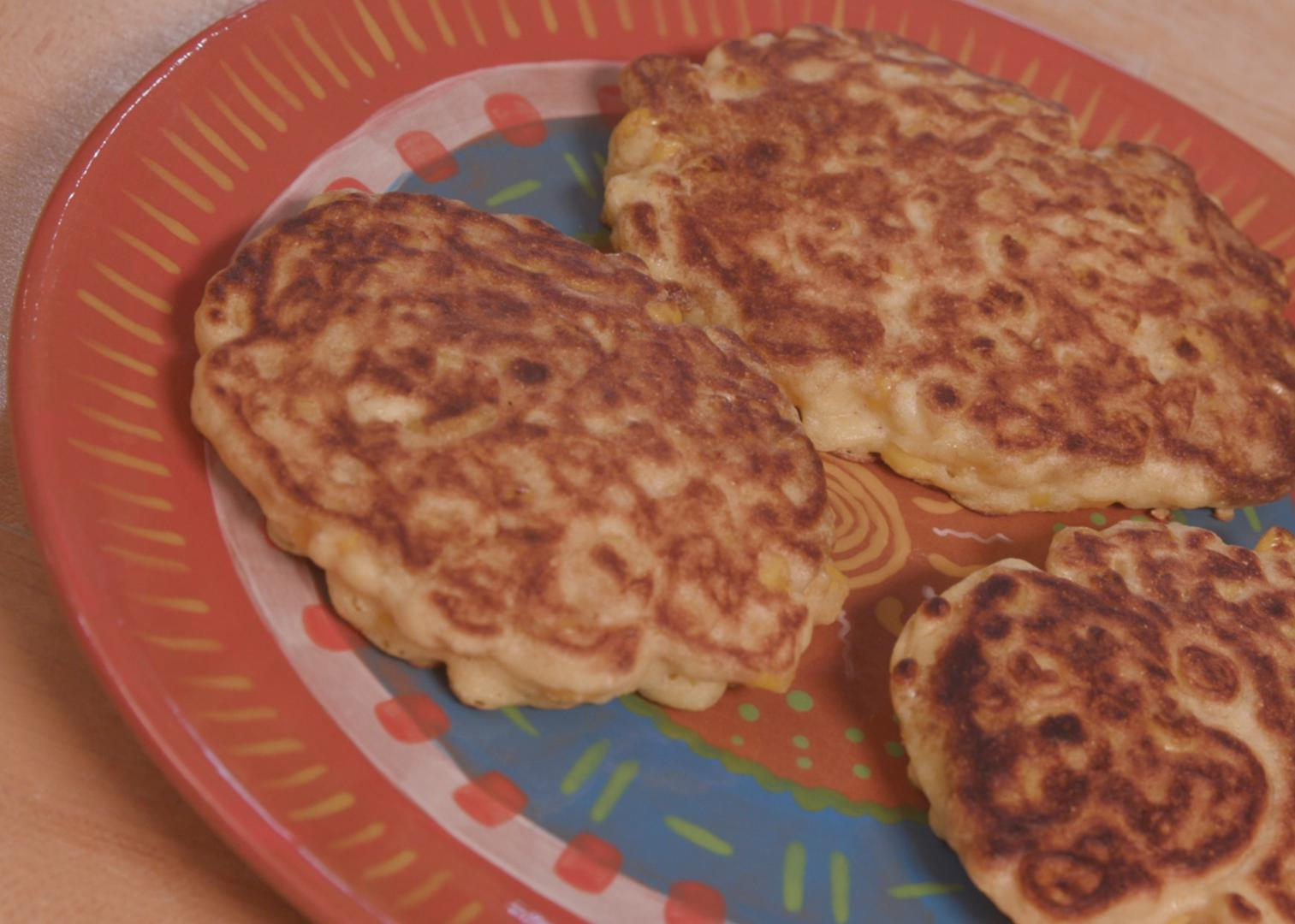 Three corn pancakes on a terra cotta plate.