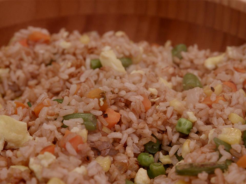 A brown bamboo bowl filled with fried rice made with brown rice, scrambled egg, and mixed vegetables including green beans, peas, carrots and corn.