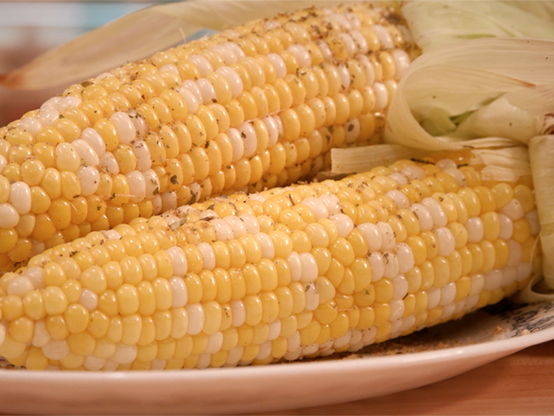Two ears of seasoned grilled corn on a platter.