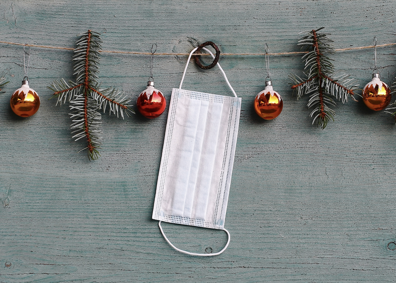 A white mask hanging on Christmas garland.