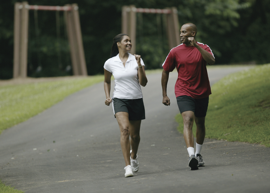 A woman and man walk for exercise.