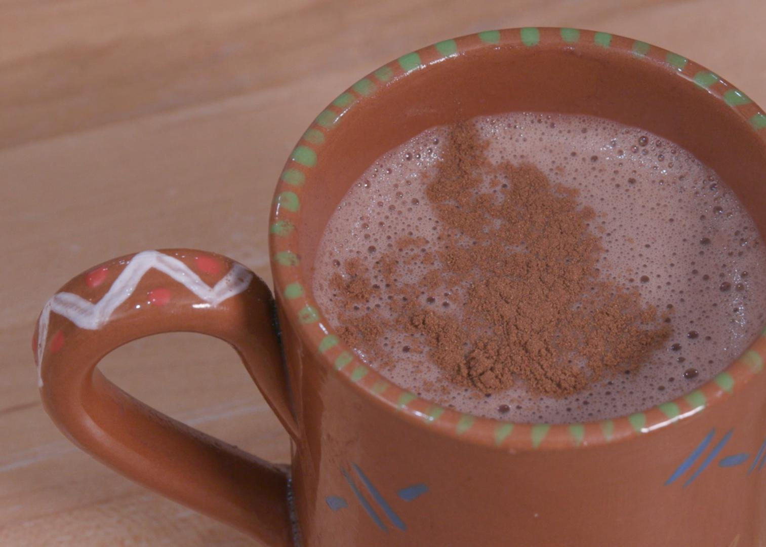 Hot cocoa sprinkled with cinnamon in a terra cotta mug