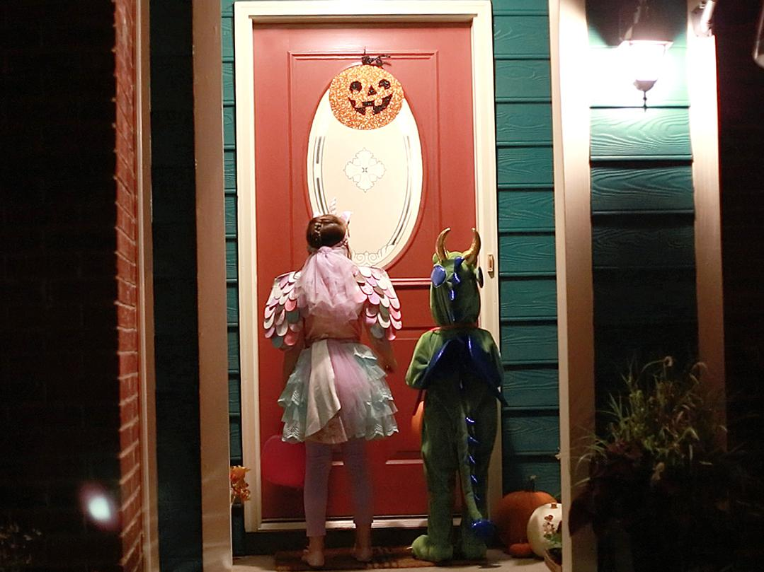 Two children waiting at a well-lit door for Halloween treats.
