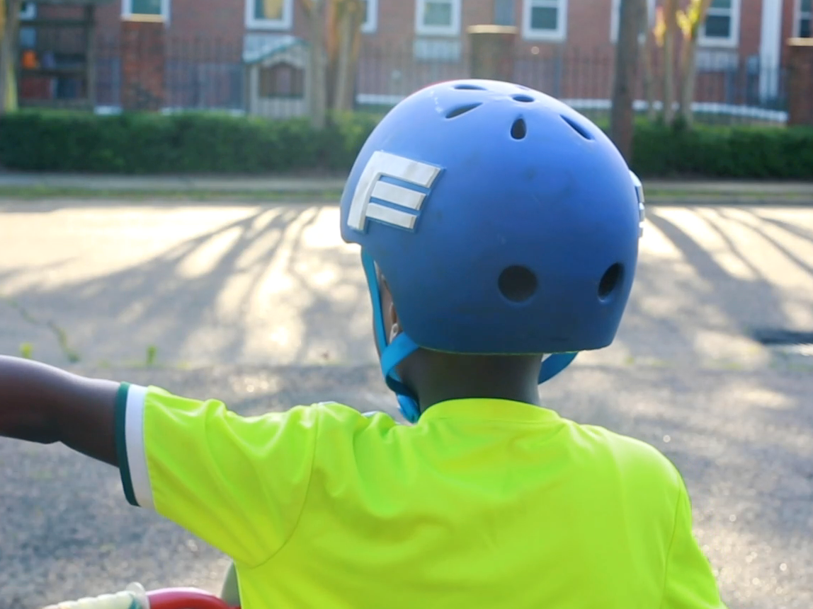 An African-American child wearing a blue helmet and neon yellow shirt extends his left hand to demonstrate a hand signal while riding a bicycle.