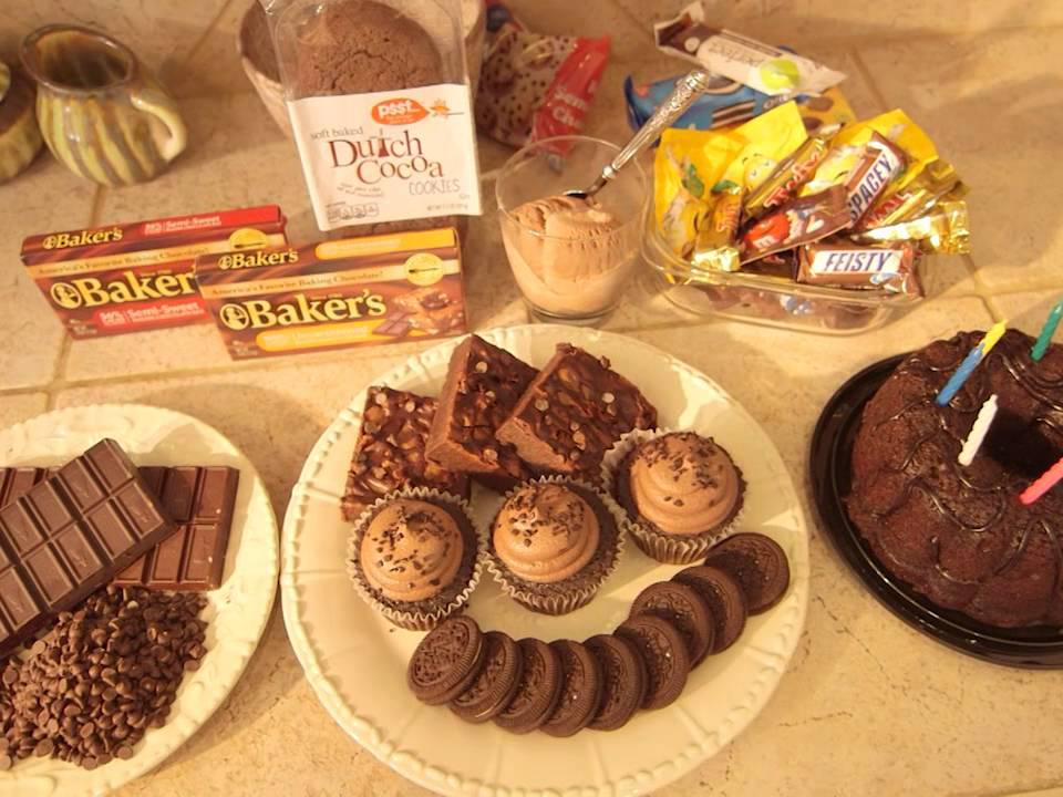 A variety of chocolate treats and baking ingredients is displayed on a kitchen counter.