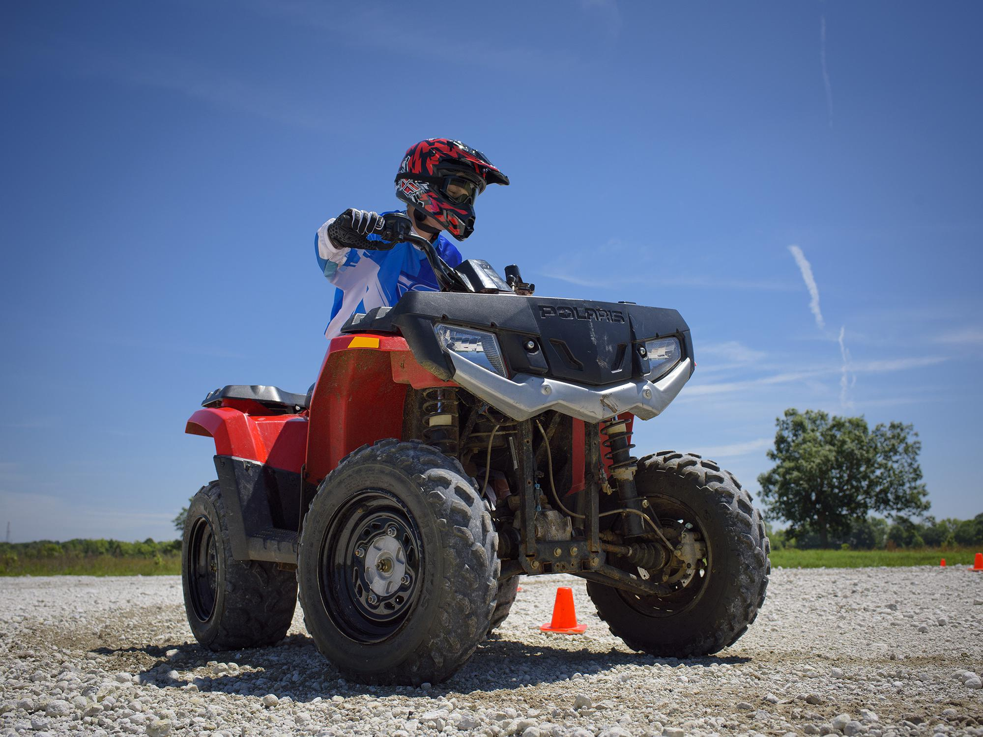 A young rider in full safety gear navigates a turn on an all-terrain vehicle.