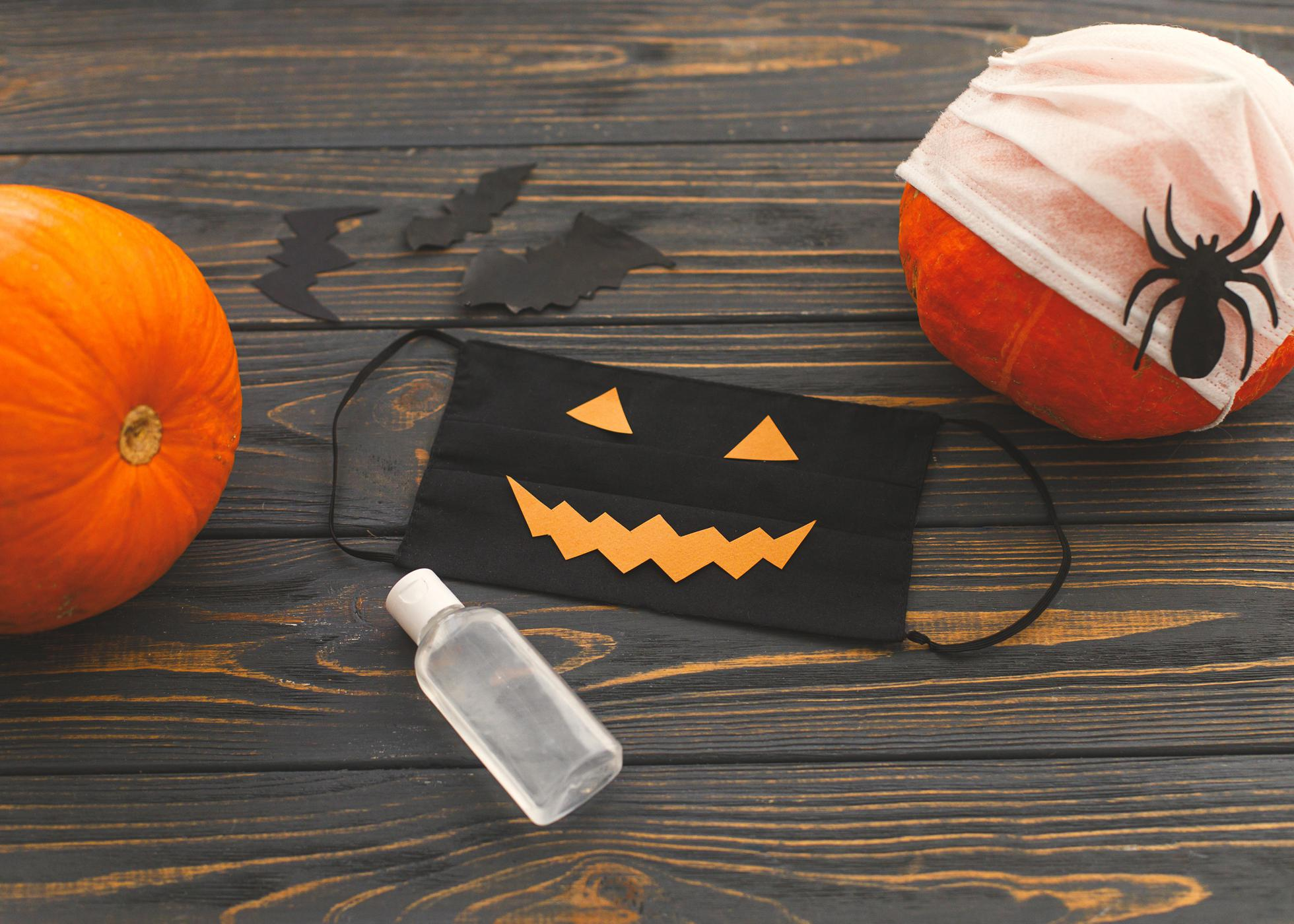 A black jack-o-lantern mask, bottle of sanitizer, and two pumpkins on a wooden backdrop.
