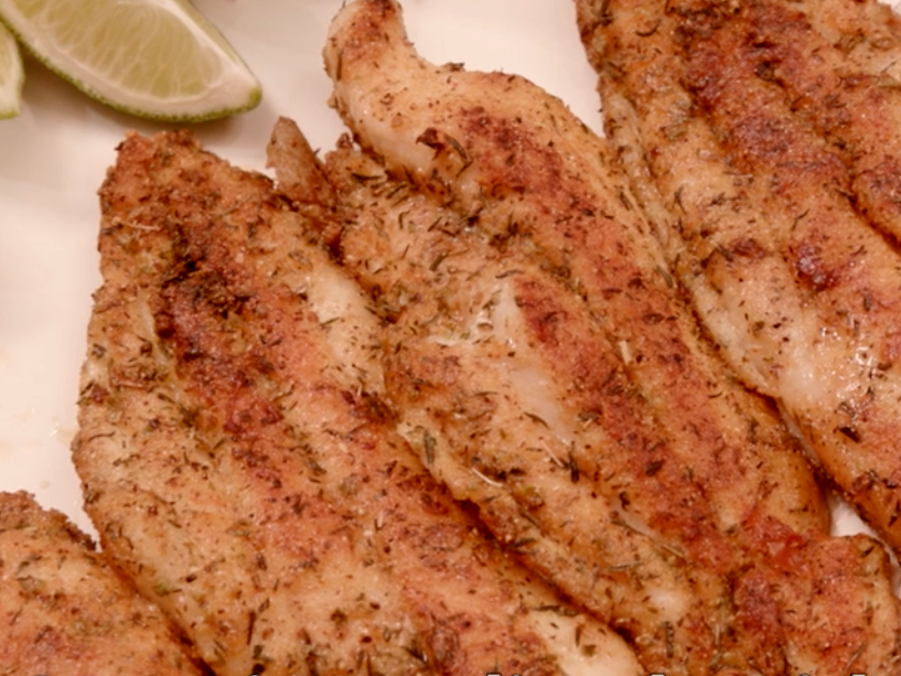 Four browned, seasoned catfish fillets on a white plate garnished with lime wedges.