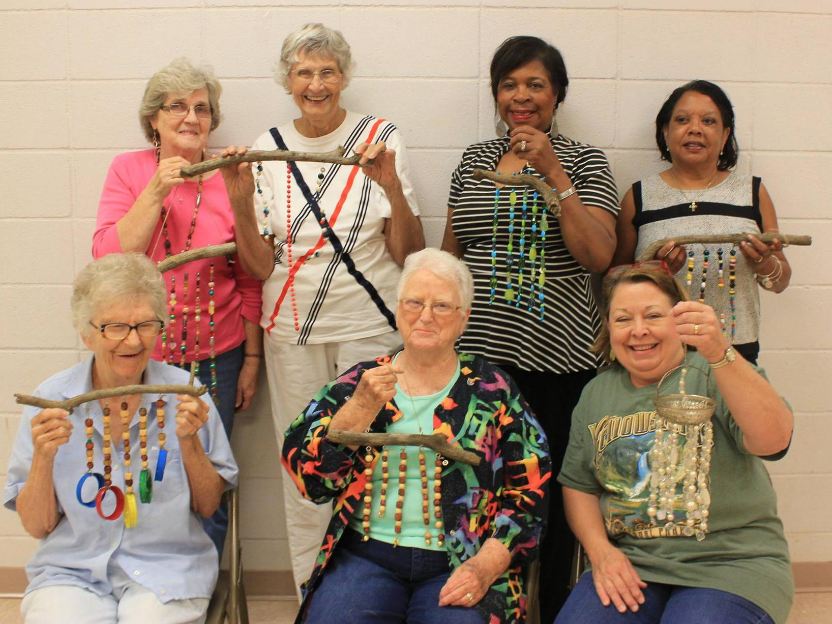 Seven women smile as they hold beaded windchimes.