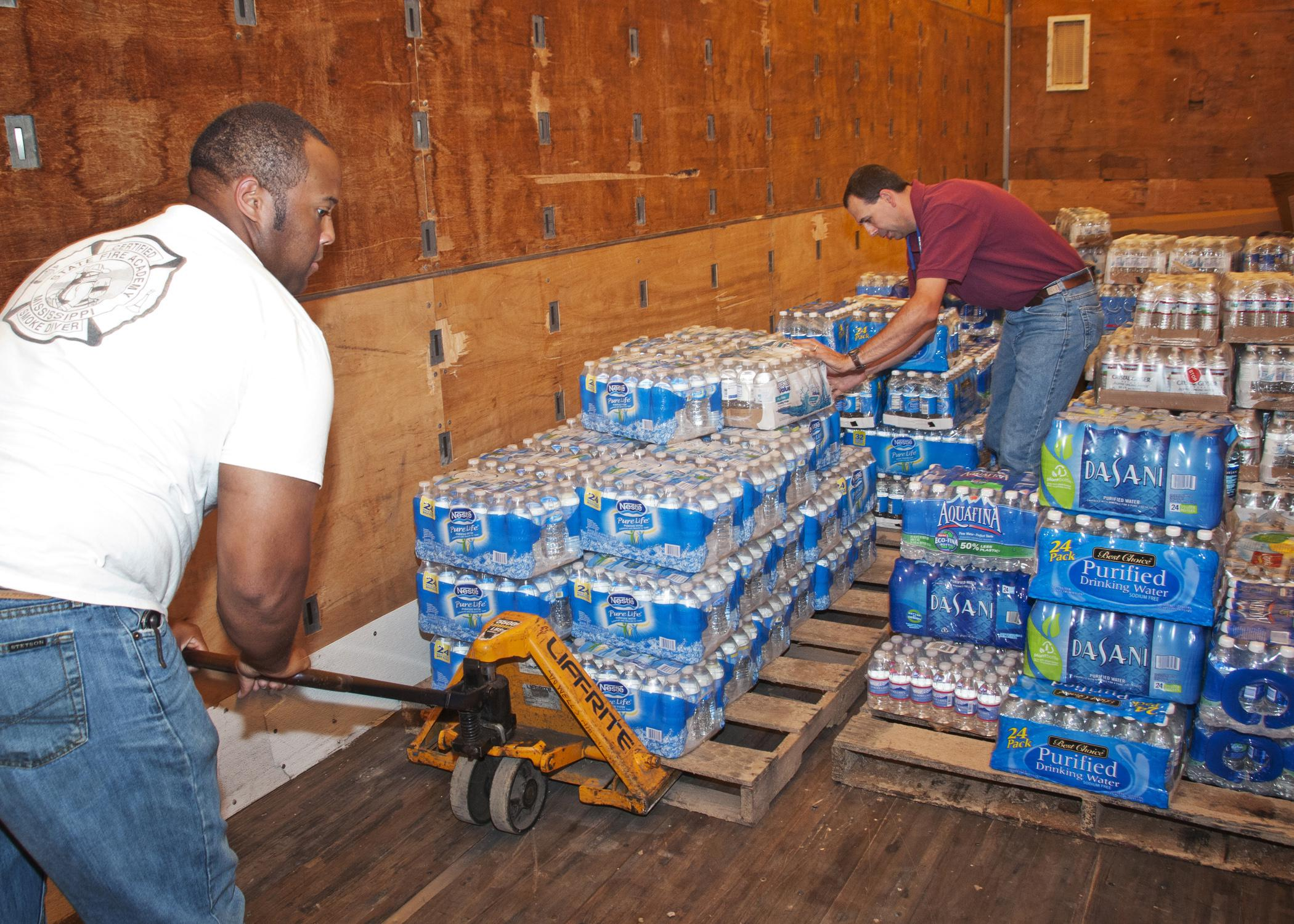 B.J. McClenton, Monroe County Extension coordinator (left), and Charlie Stokes, area Extension agent, unload water from a semi-trailer to distribute to tornado victims in Monroe County in 2011. (Photo by MSU Ag Communications/Scott Corey)