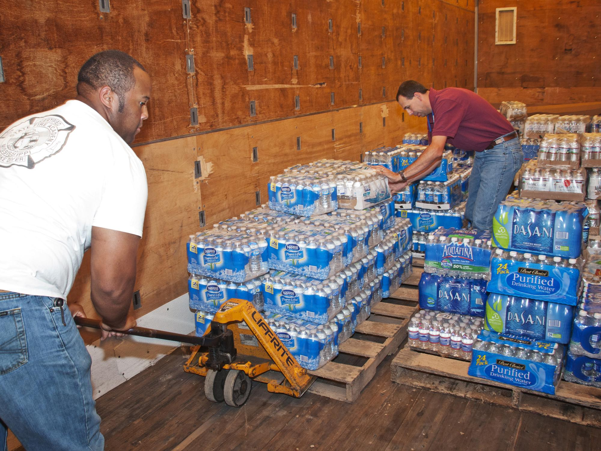 Two men move cases of bottled water in a storehouse.