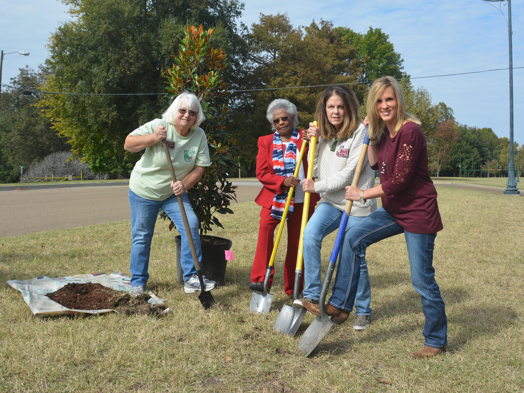 Four women, each with a foot on her shovel, look at the camera as they prepare to dig a hole for a small tree.