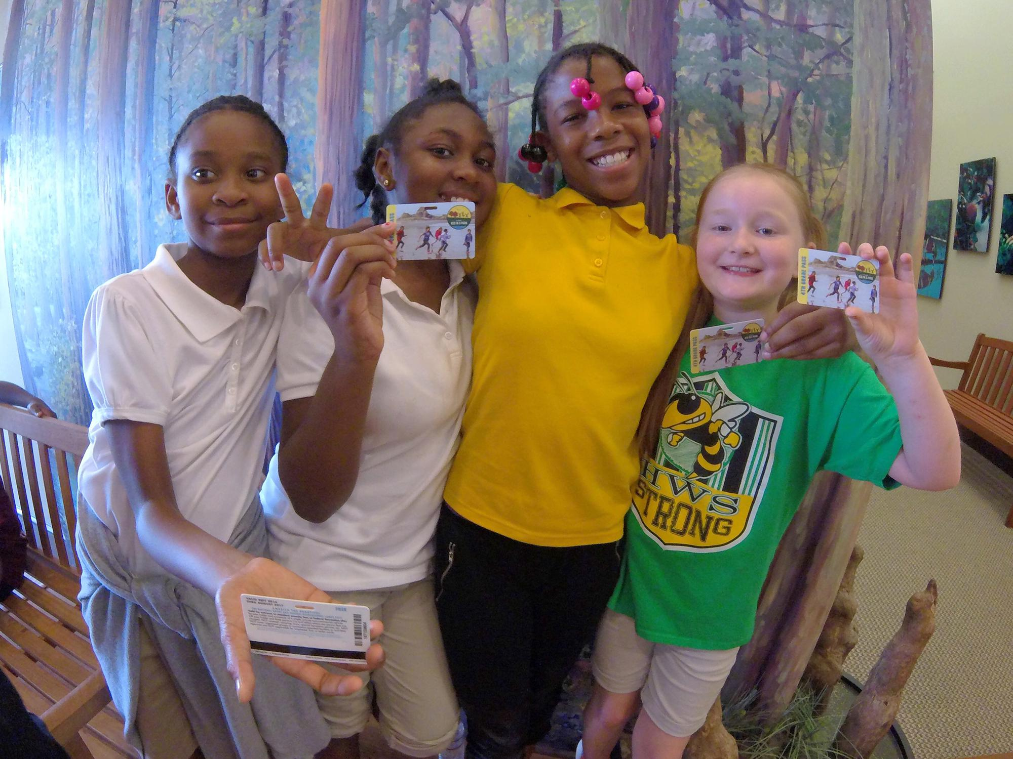 Four fourth-grade girls show off their personal identification cards that are passes to federal parks.