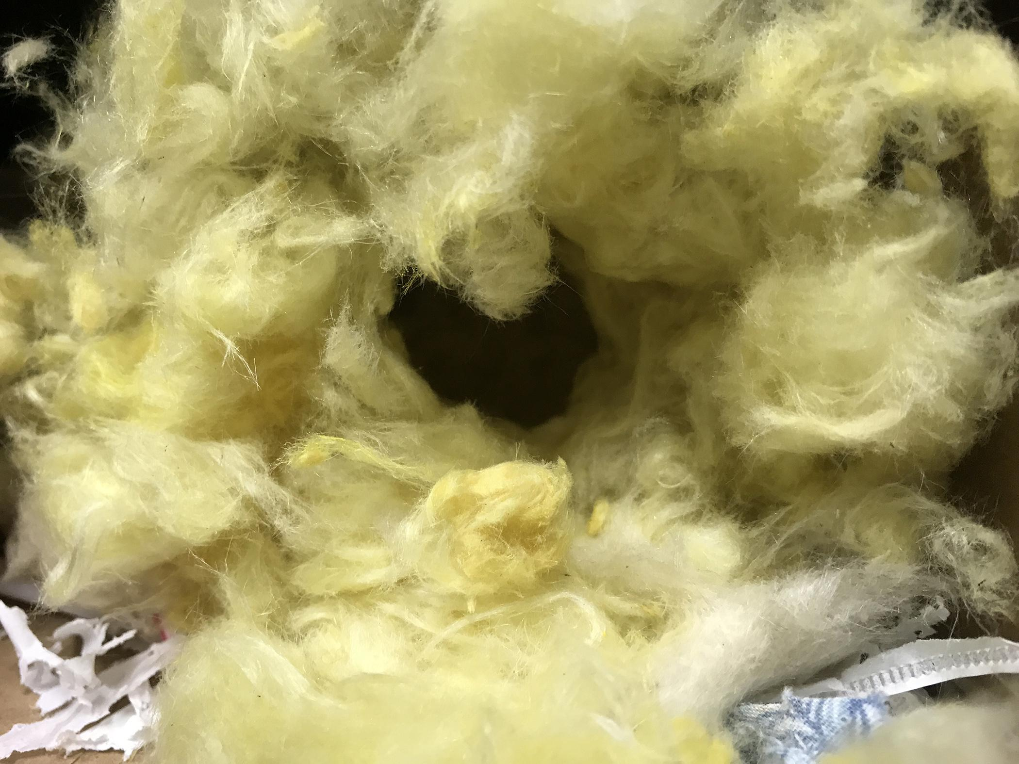 a nest built by mice using insulation and a variety of other materials
