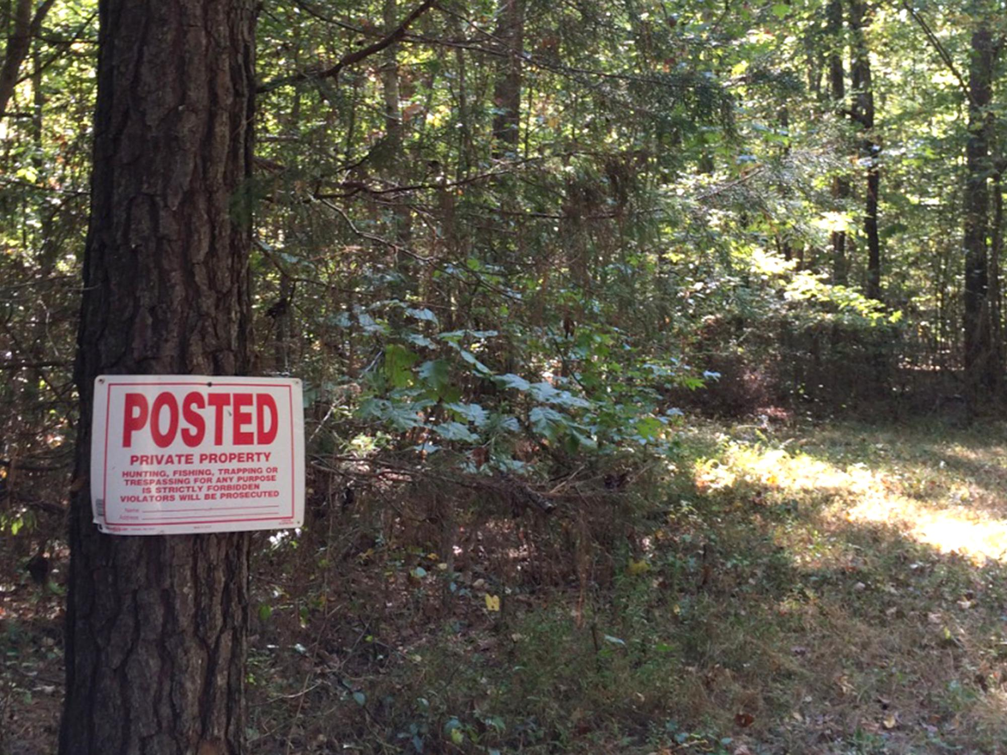 "A sign nailed to a pine tree in a wooded area that reads, ""POSTED PRIVATE PROPERTY."""