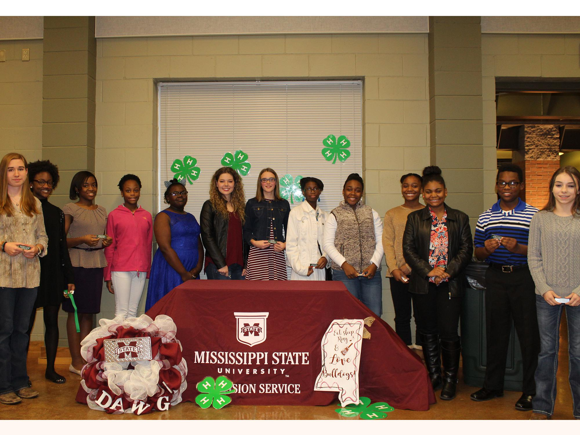 A group of teenagers pose for a photo celebrating their induction as 4-H Leadership team members.