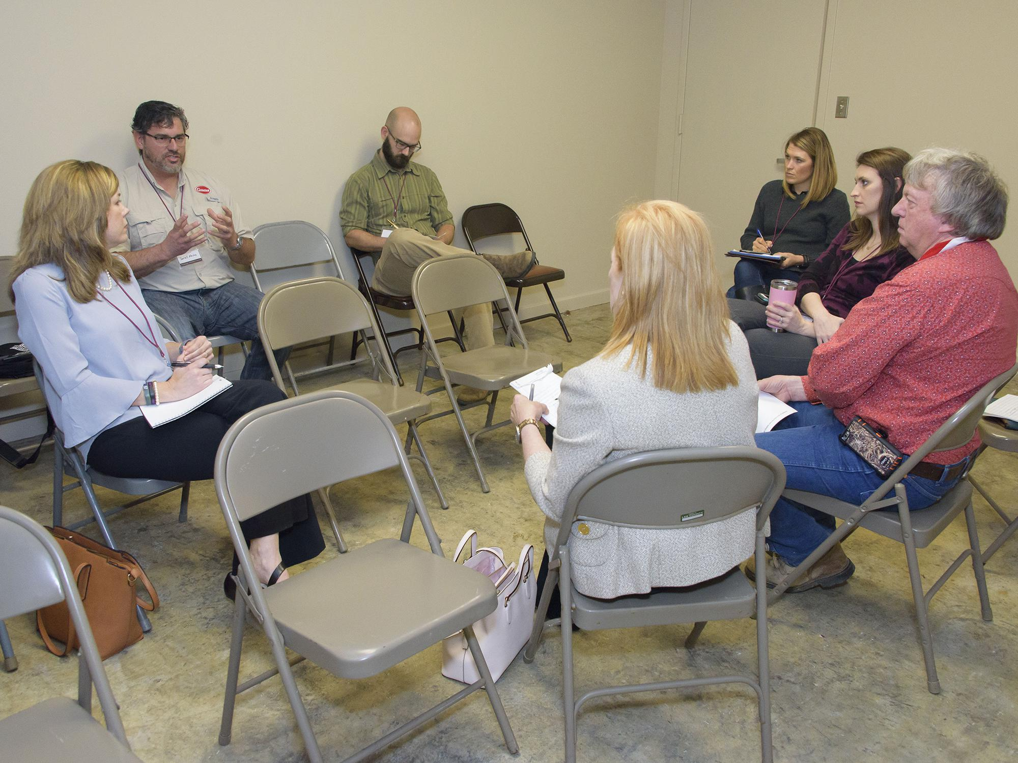Man in glasses speaking to a group of people sitting in a circle.