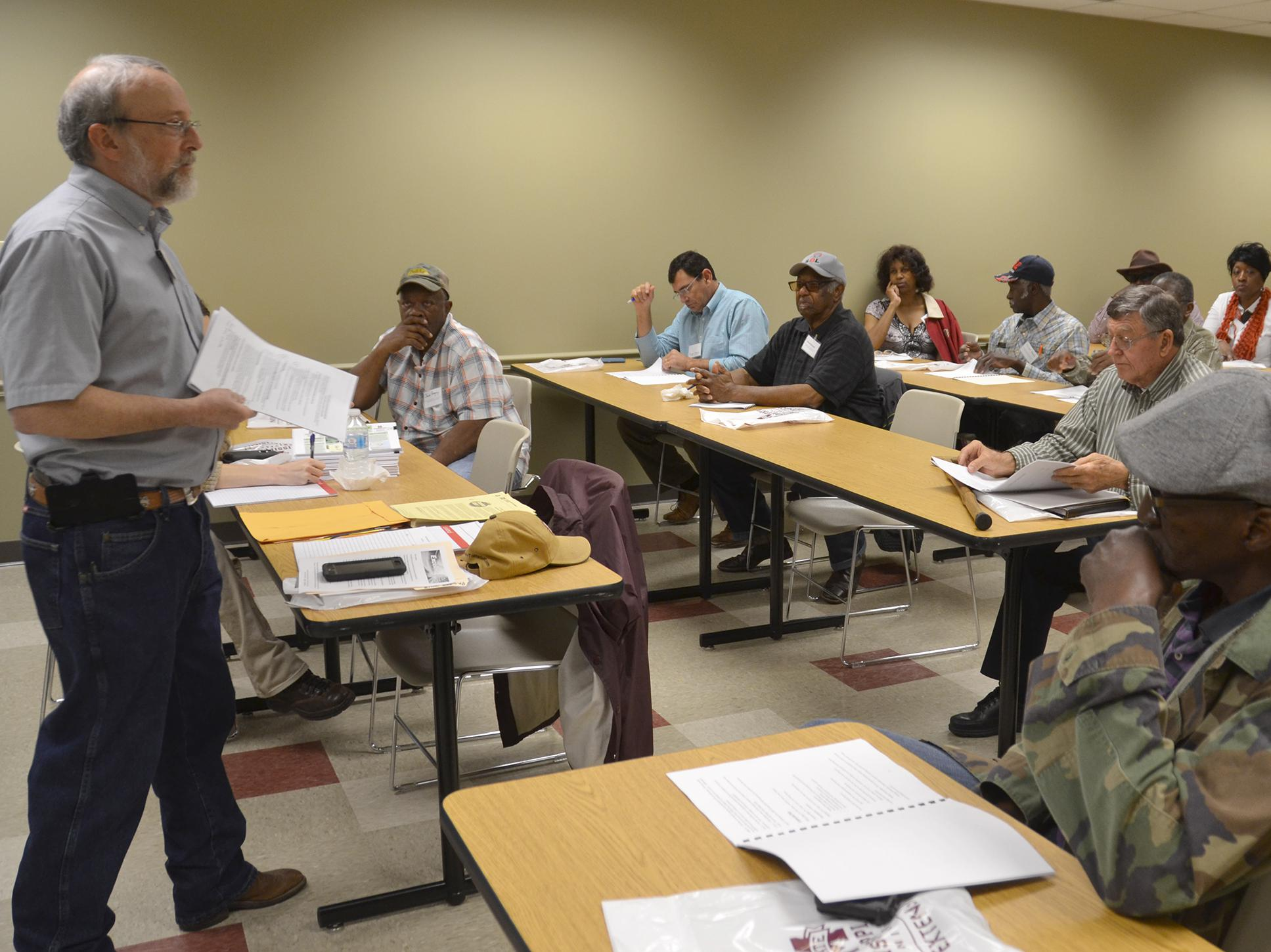 A Mississippi State University specialist stands before a room of seated meeting participants.