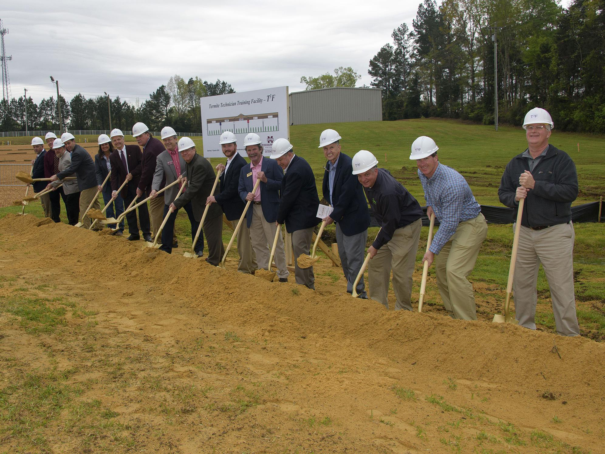 A group of more than a dozen people in hard hats break ground with shovels.