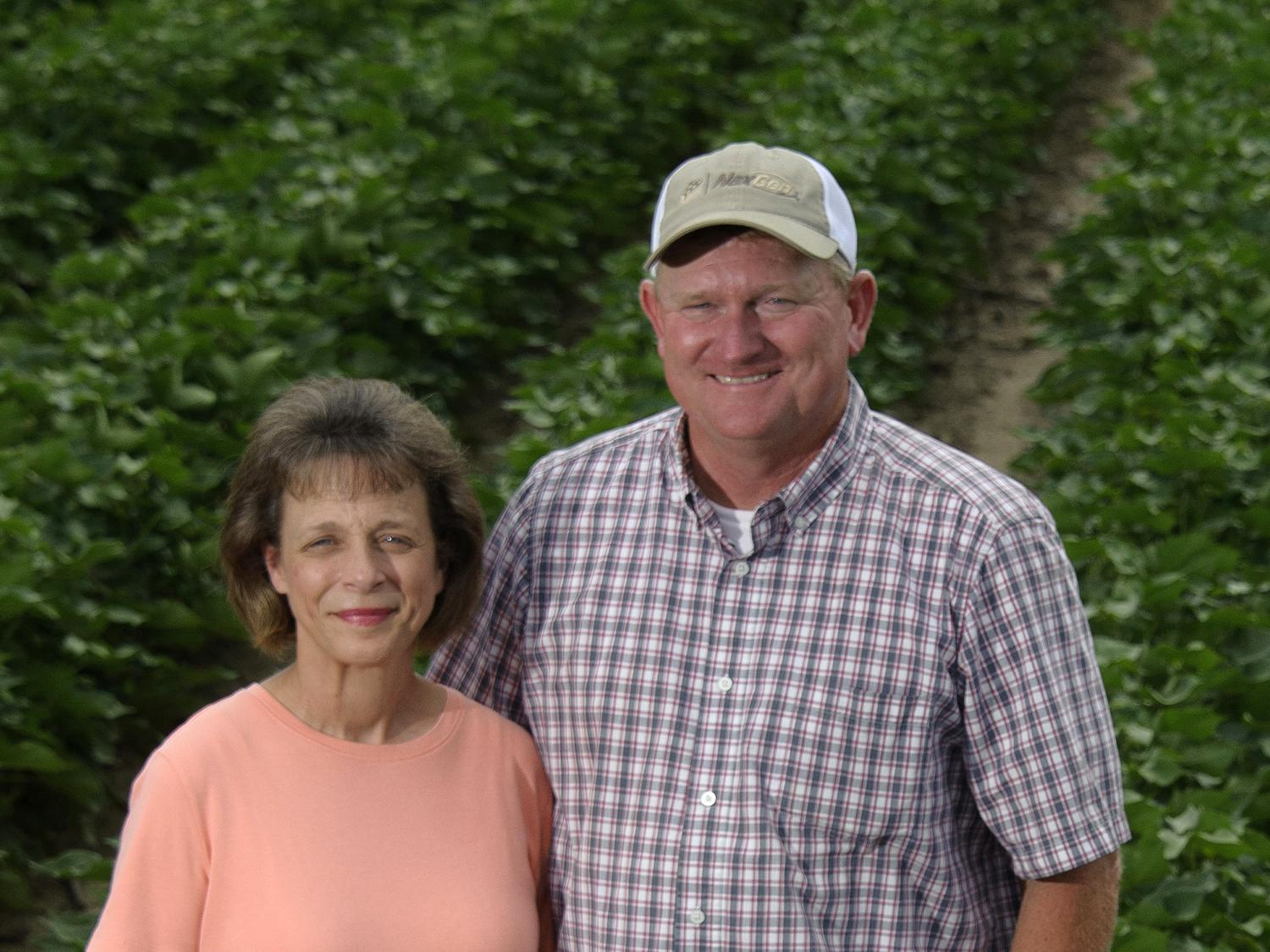 A wife and husband stand in a field with cotton rows.