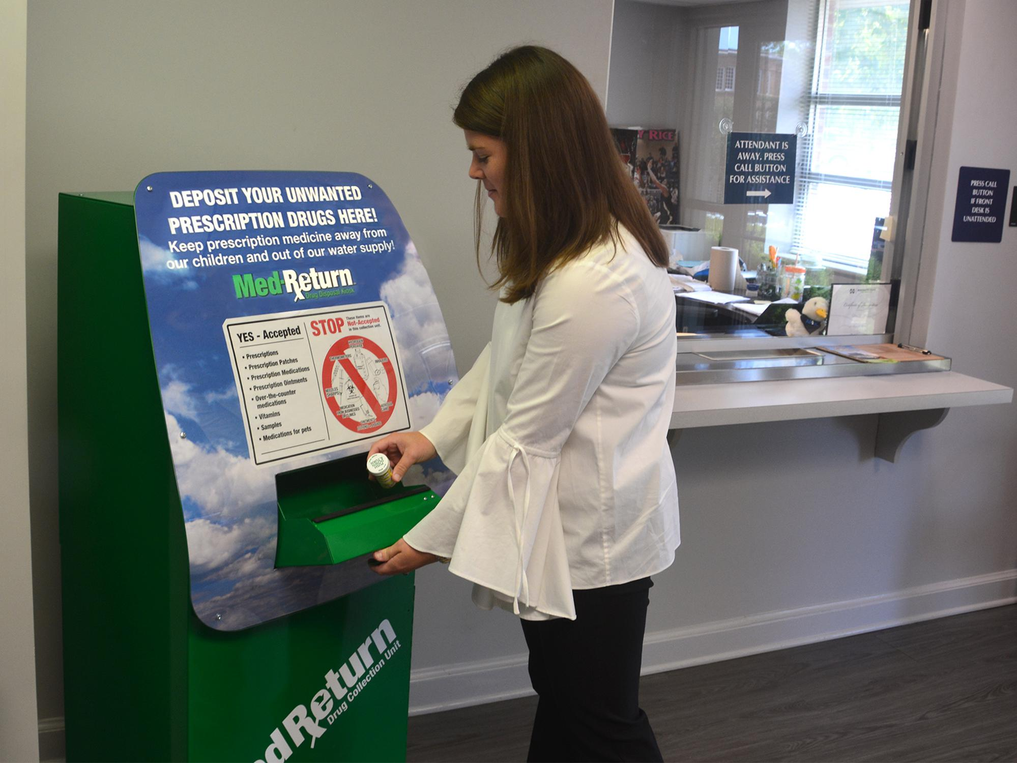 Young woman places a prescription bottle in secure slot in a large, green metal box