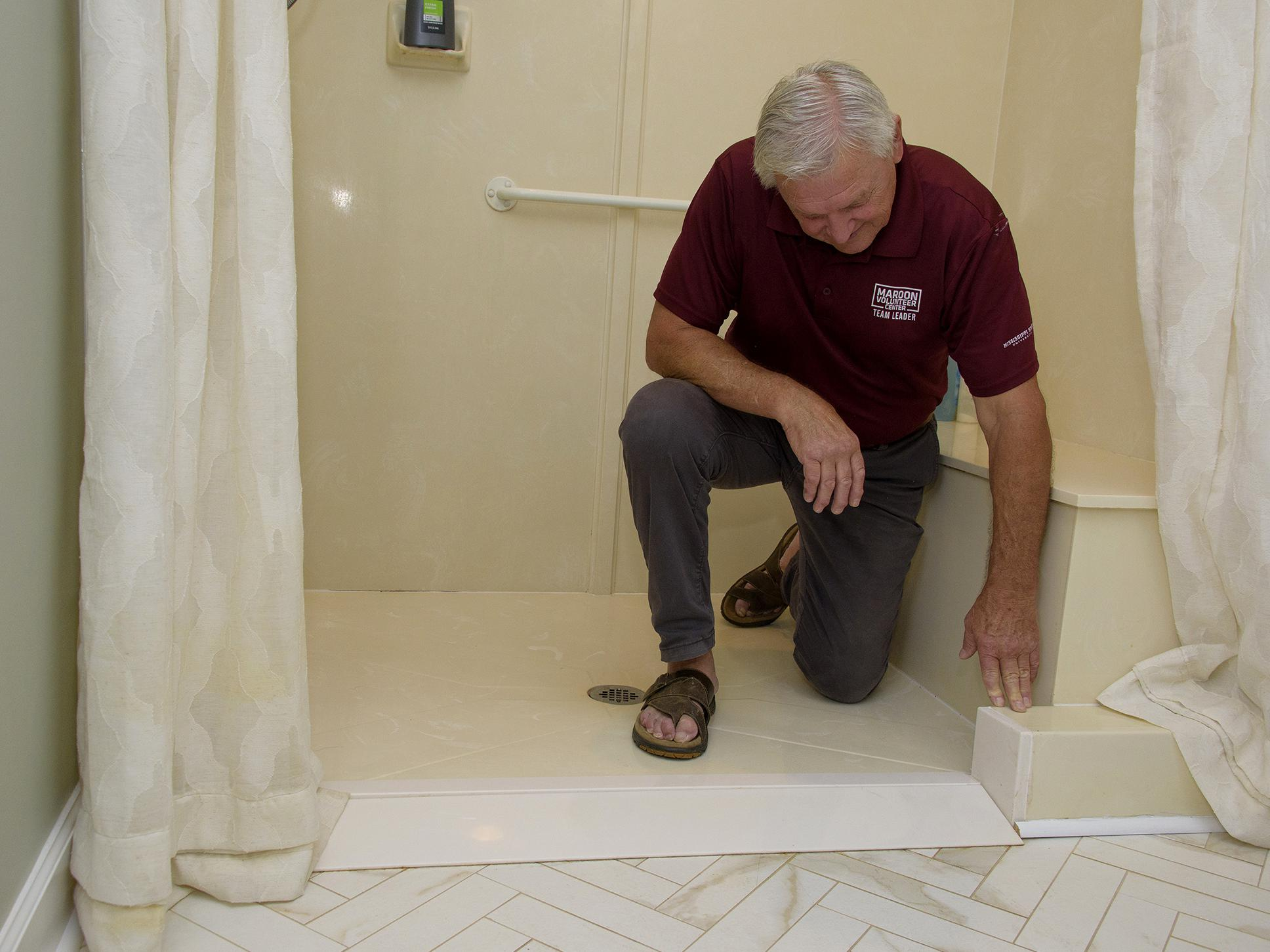 A man kneels in a walk-in shower, reaching down to a point in the entryway.