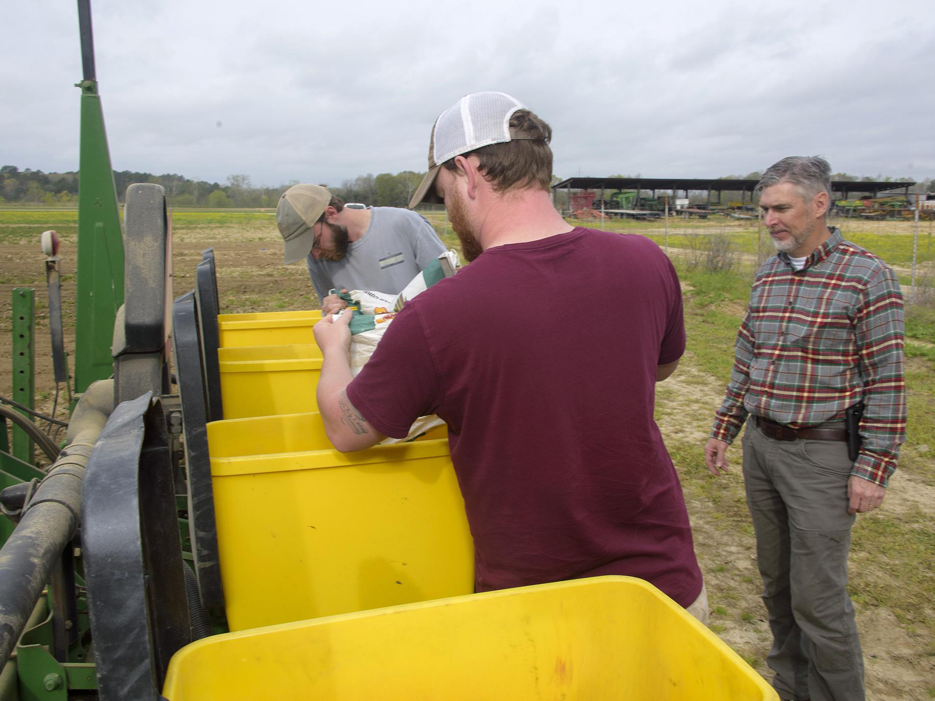 Two young men pour seed into bright yellow bins while a man watches.