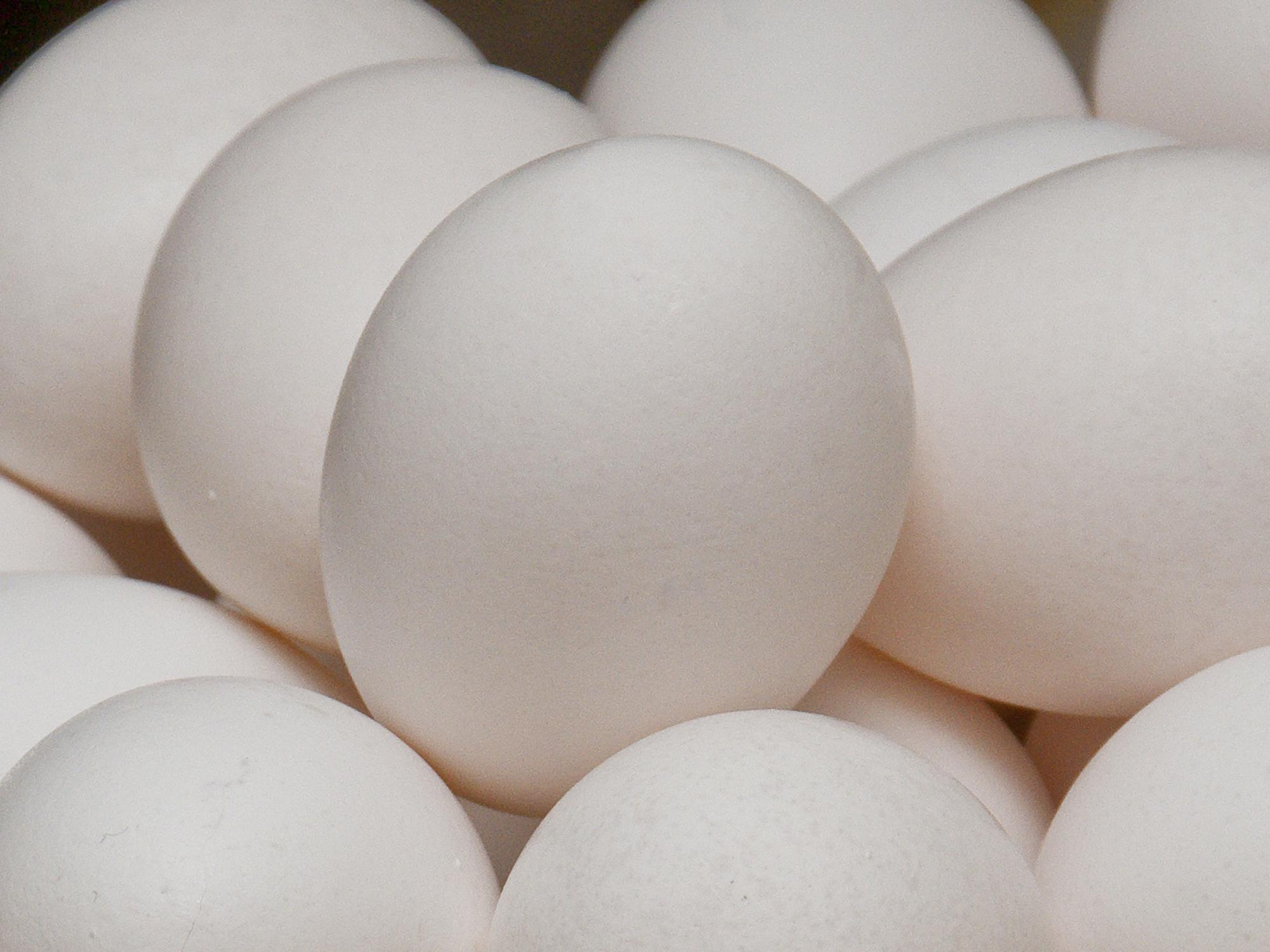 A close up of white eggs stacked in a bowl with other white eggs.