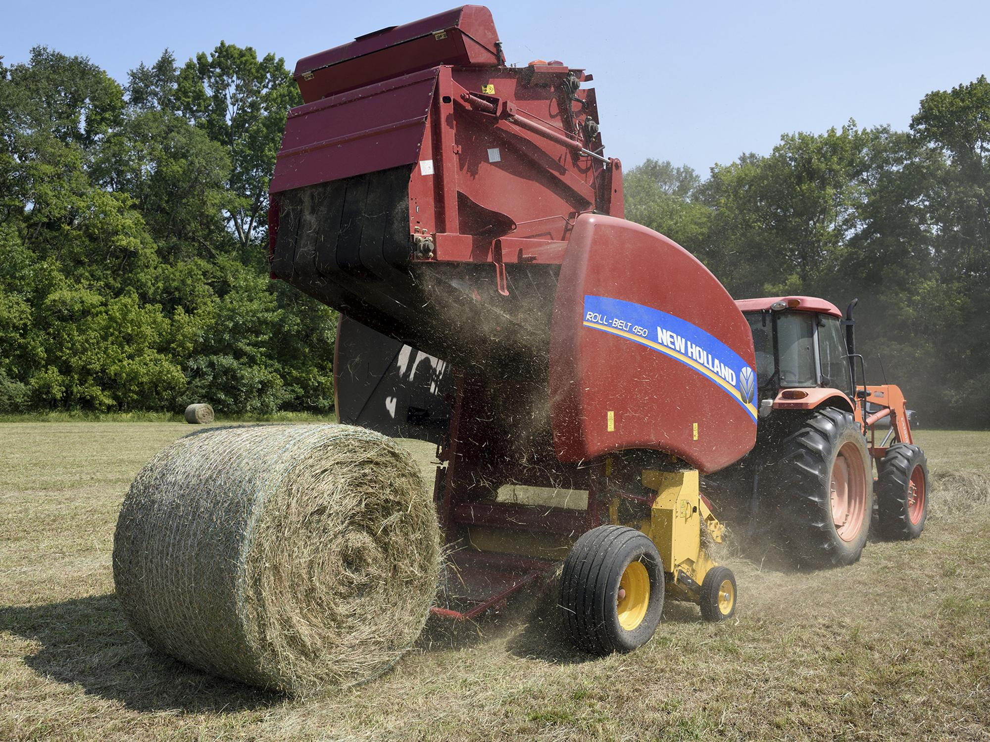 A red baler hitched to the back of an orange tractor drops a new, round bale of hay into a field.