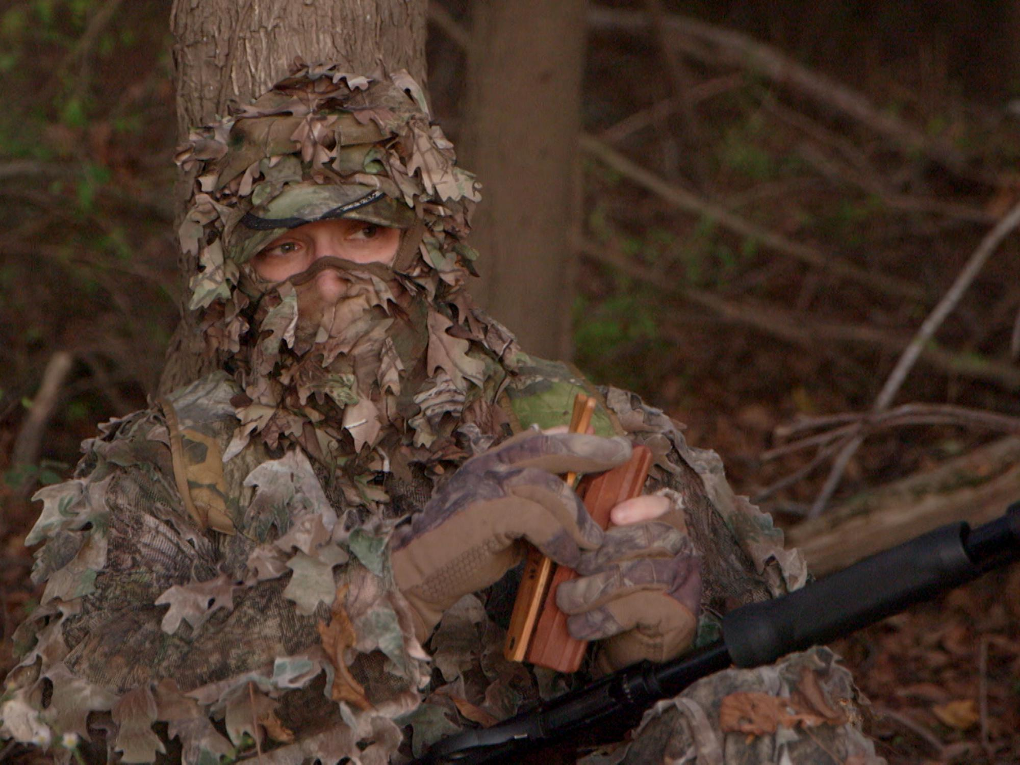 Only the eyes of a turkey hunter wearing full camouflage is visible. He is holding a wooden turkey caller.