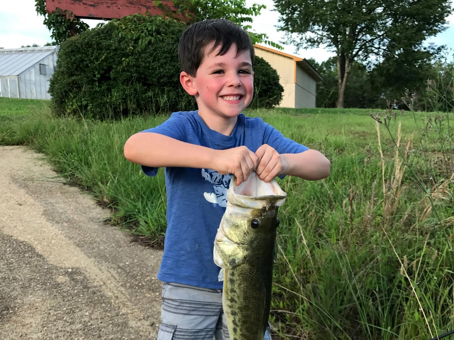 Young boy in blue shirt holding large fish.