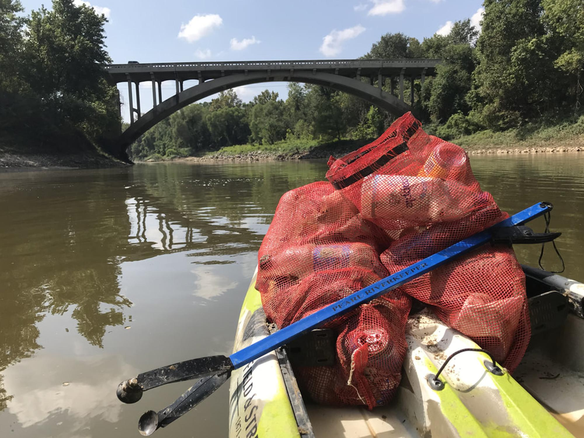 """The front of a kayak has two red meshed bags containing litter and a blue trash-grabbing tool with the words """"Pearl Riverkeeper"""" printed on it. The boat is on a small river and approaching a highway bridge."""