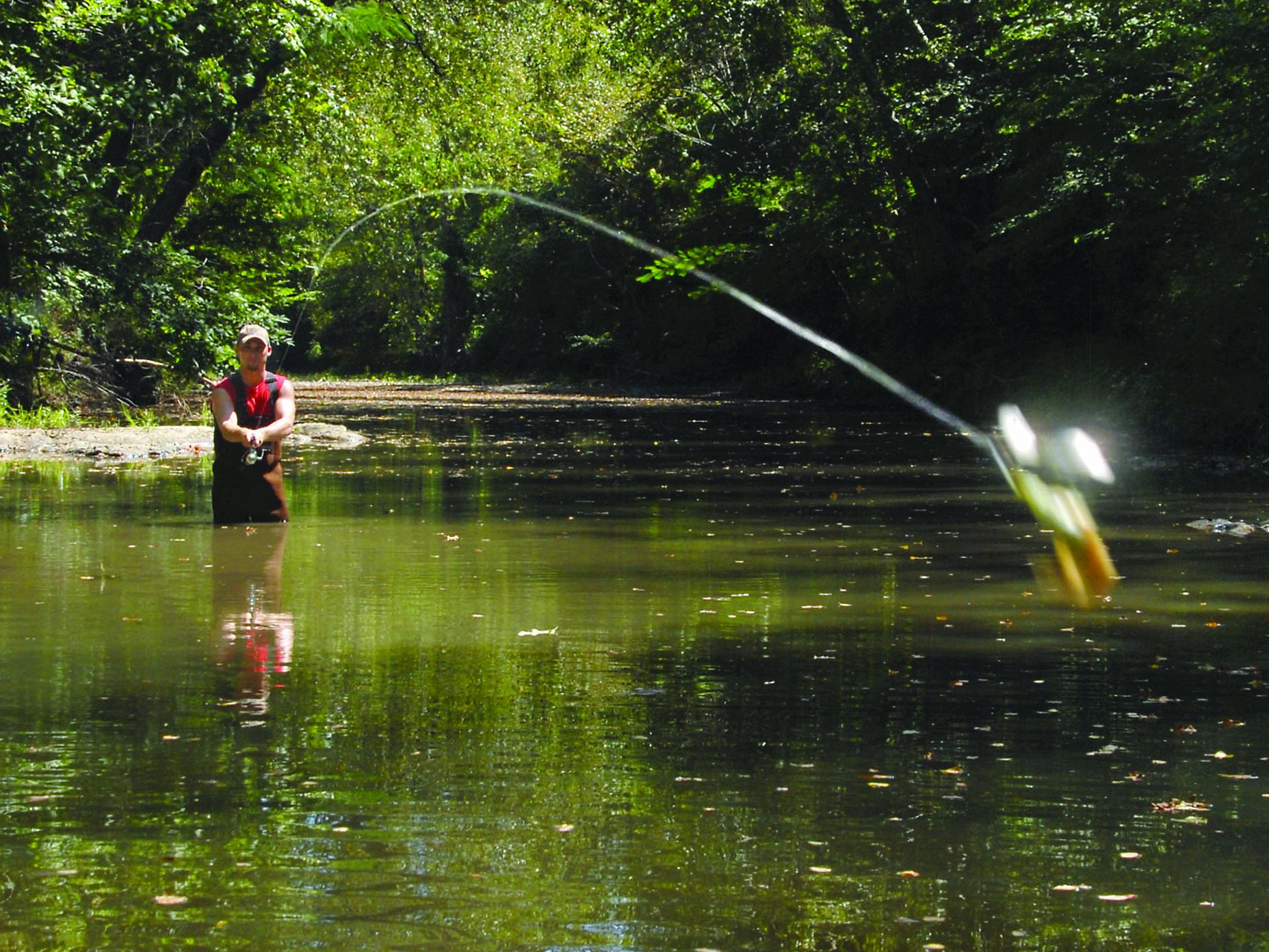 A fisherman in rubber waders stands in a small, quiet stream and casts a lure toward the viewer.