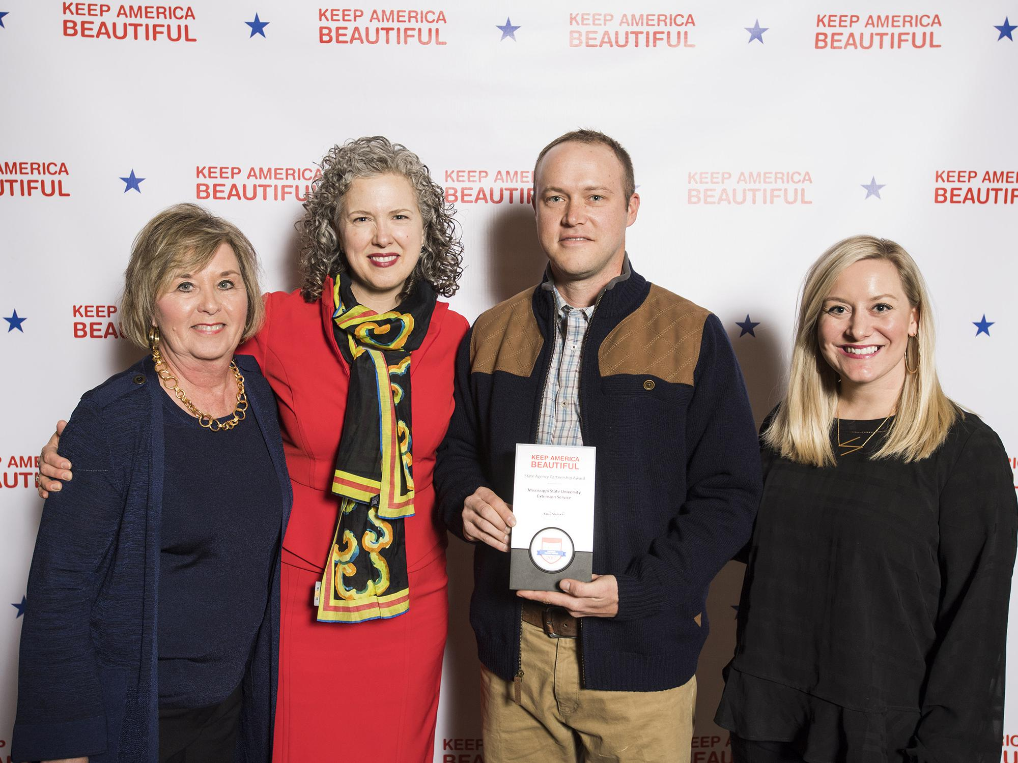 Four people pose for a photo with the award presented to the Mississippi State University Extension Service for its support of the Wildflower Trails of Mississippi Project.
