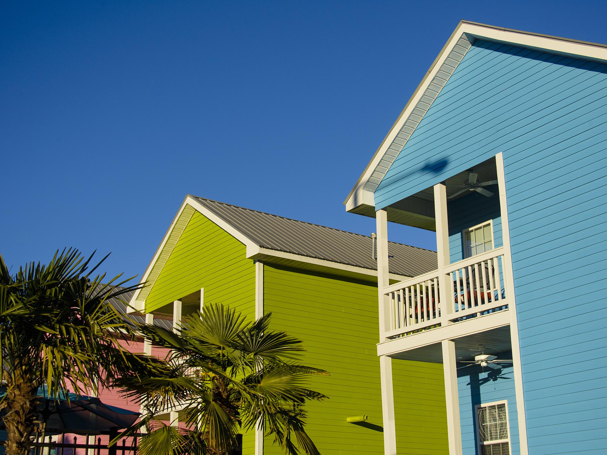 Palm trees adorn the landscape in front of blue, green and pink cottages.