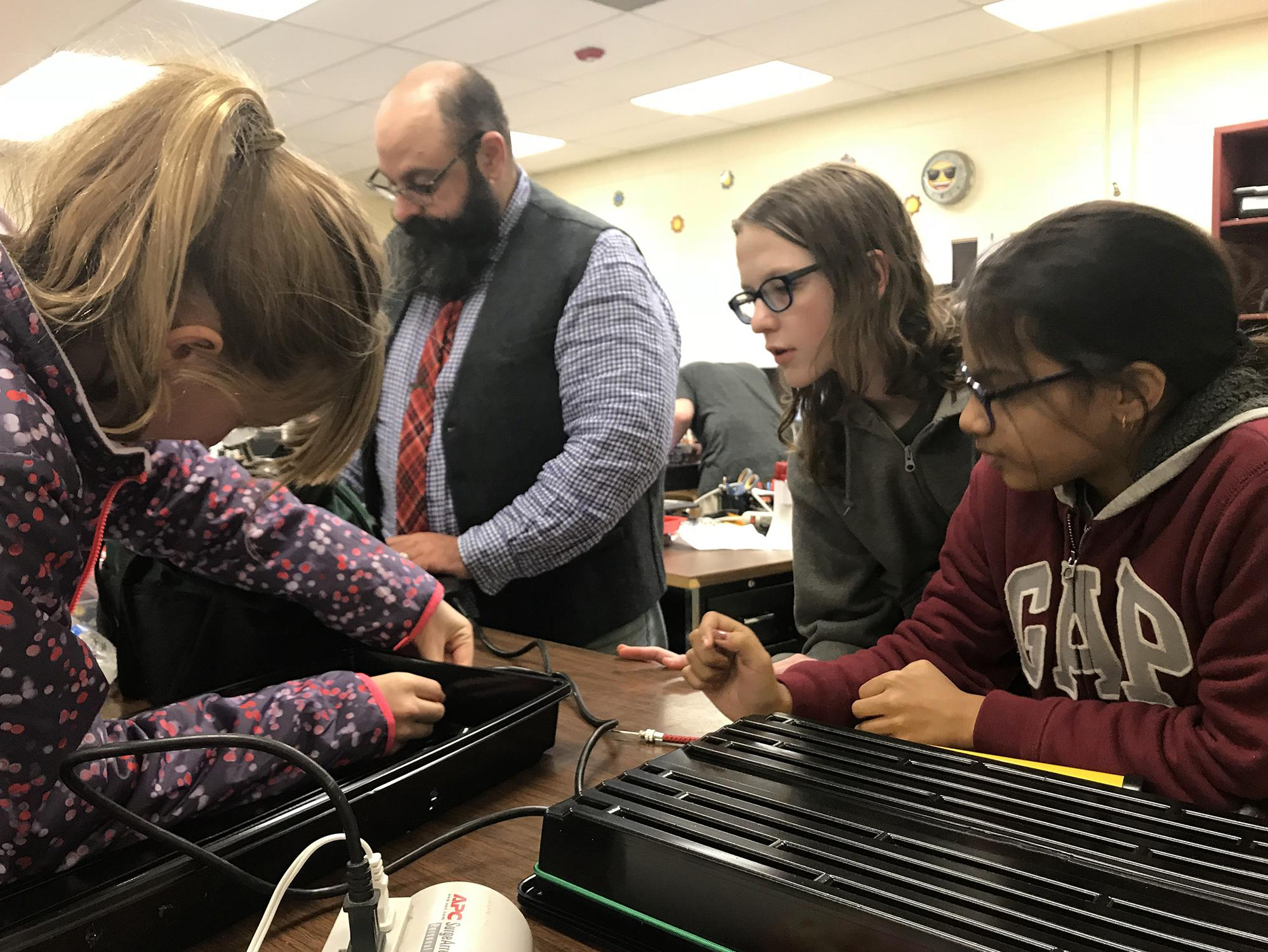 Two middle-school-aged girls and a middle-aged male teacher look on at another girl poking a hole in the side of a black tray for a science project.