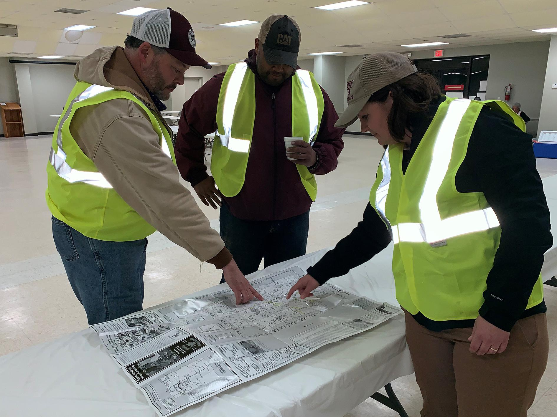 Two men and a woman, all wearing baseball caps and reflective yellow vests, look at a roadmap spread out on a table in a large, empty, well-lit room.