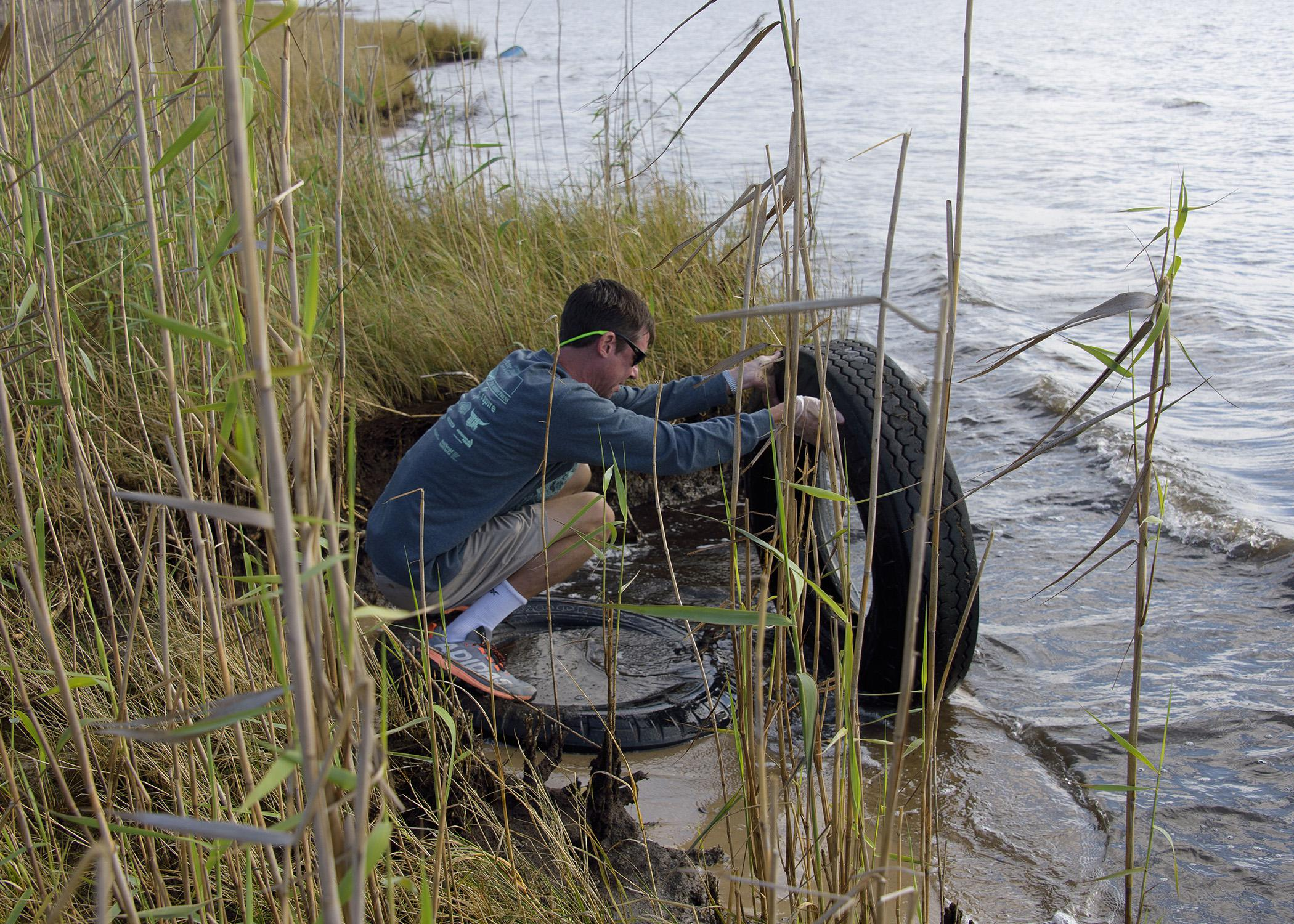 A man kneeling in tall grass picks up a tire out of water.