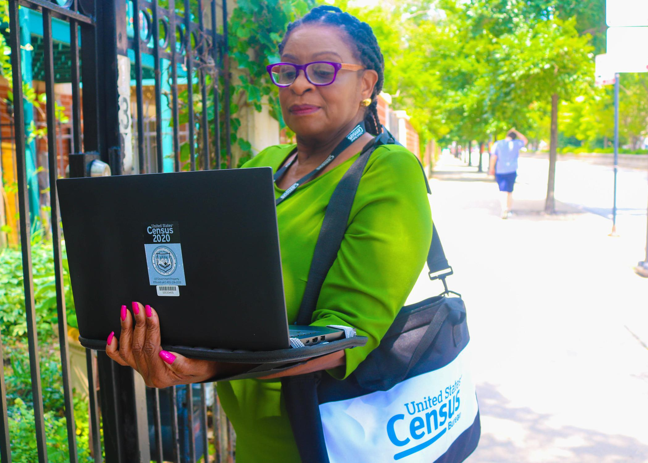 Woman in a green dress with a bag around her shoulder stands in front of a gate holding a laptop computer.