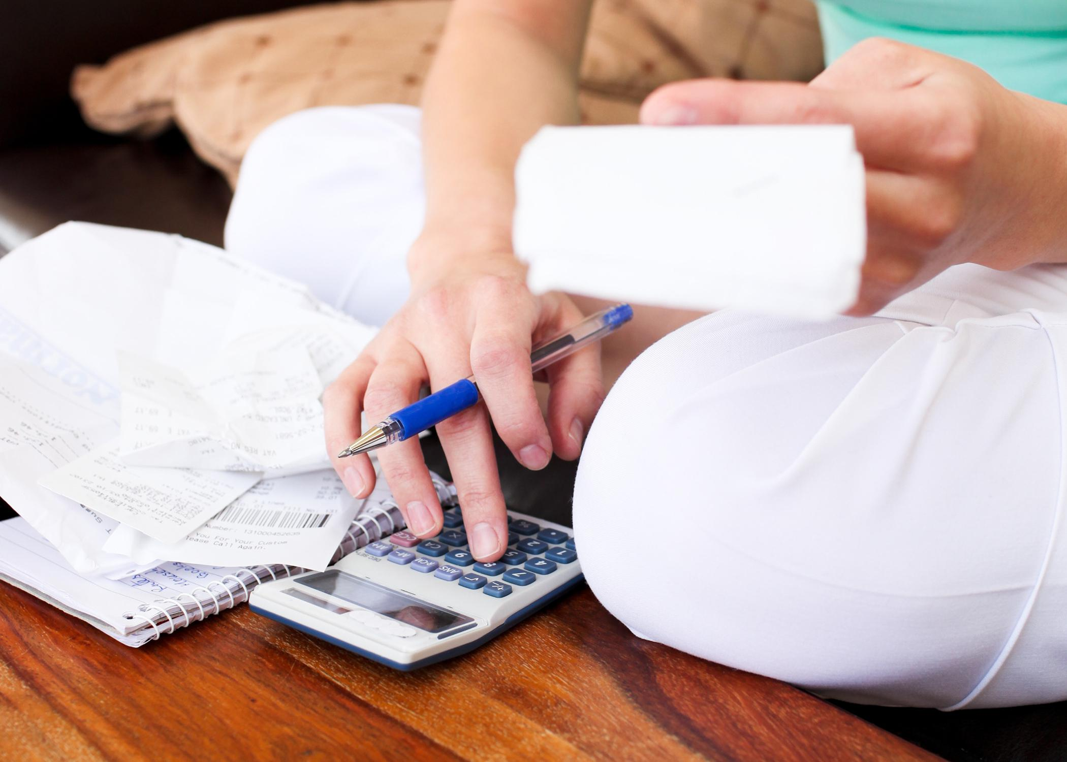 Closeup of a woman budgeting personal finances.