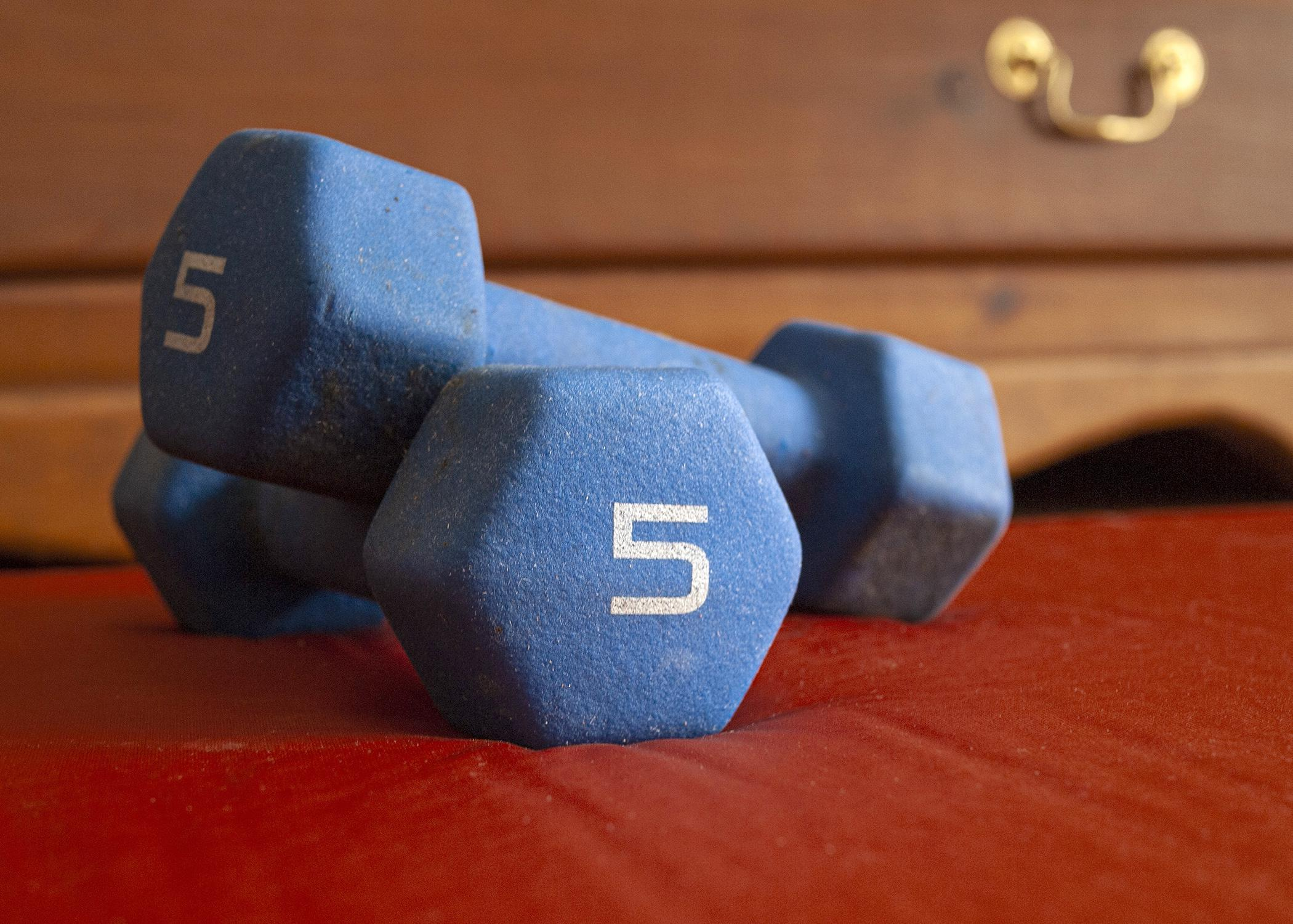 Two blue dumbbells are stacked on a bedroom floor.