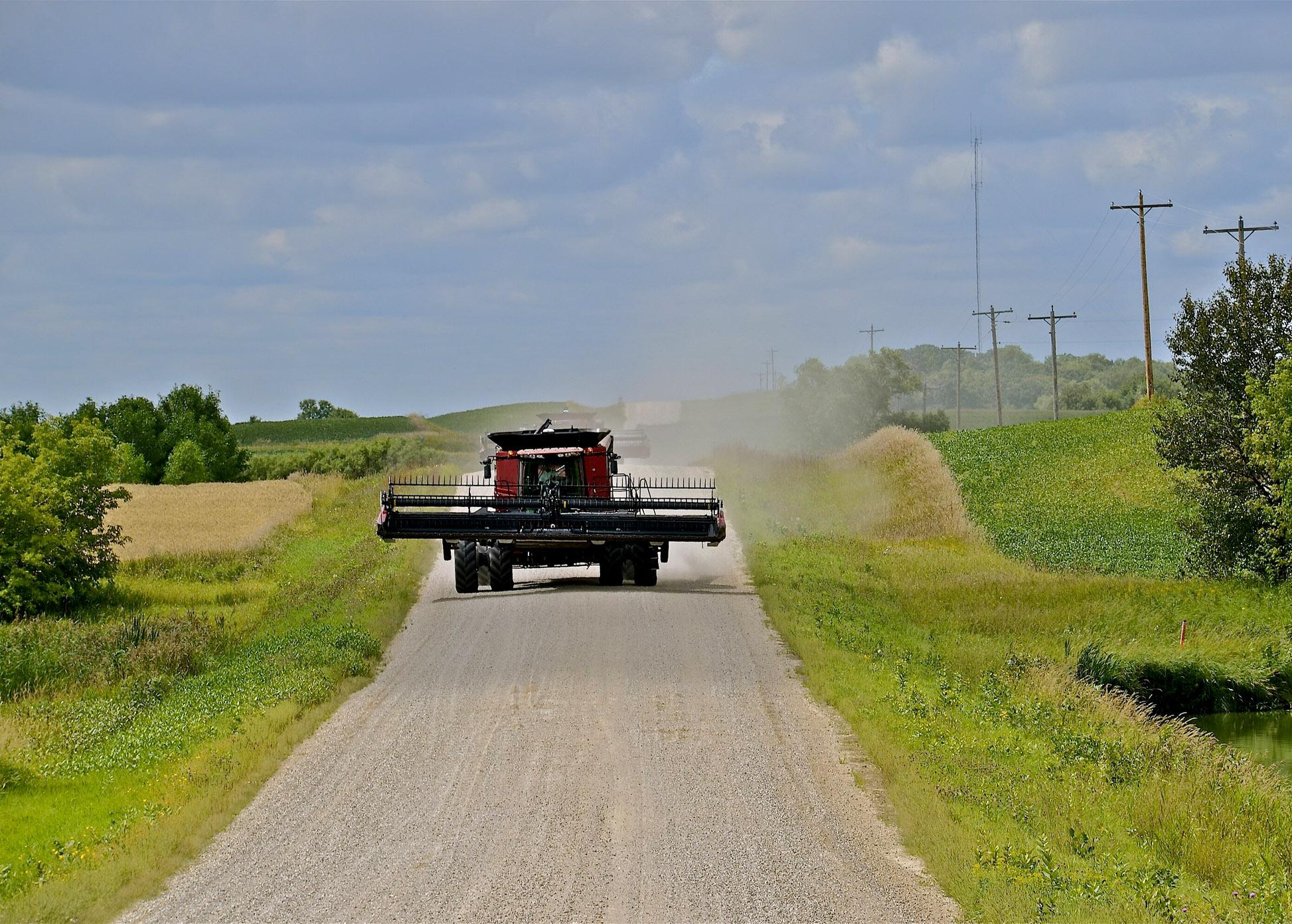 A red combine drives down a gravel road with farmland on both sides.