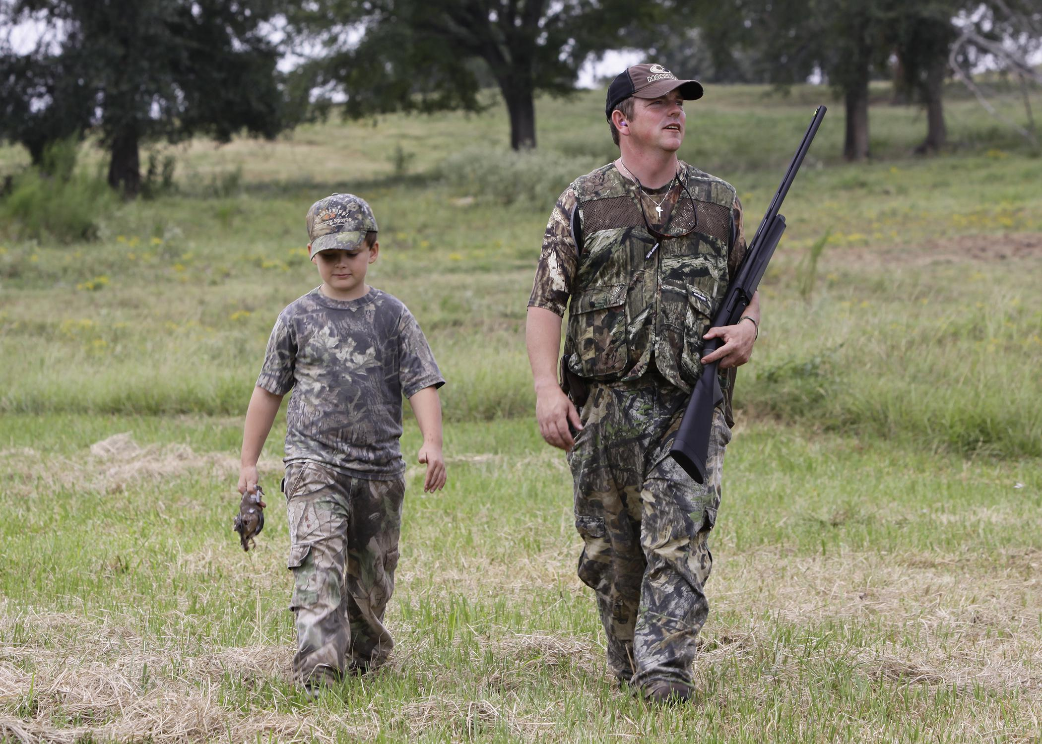 A man holding a shotgun and a boy dressed in camouflage walk in a grassy meadow.