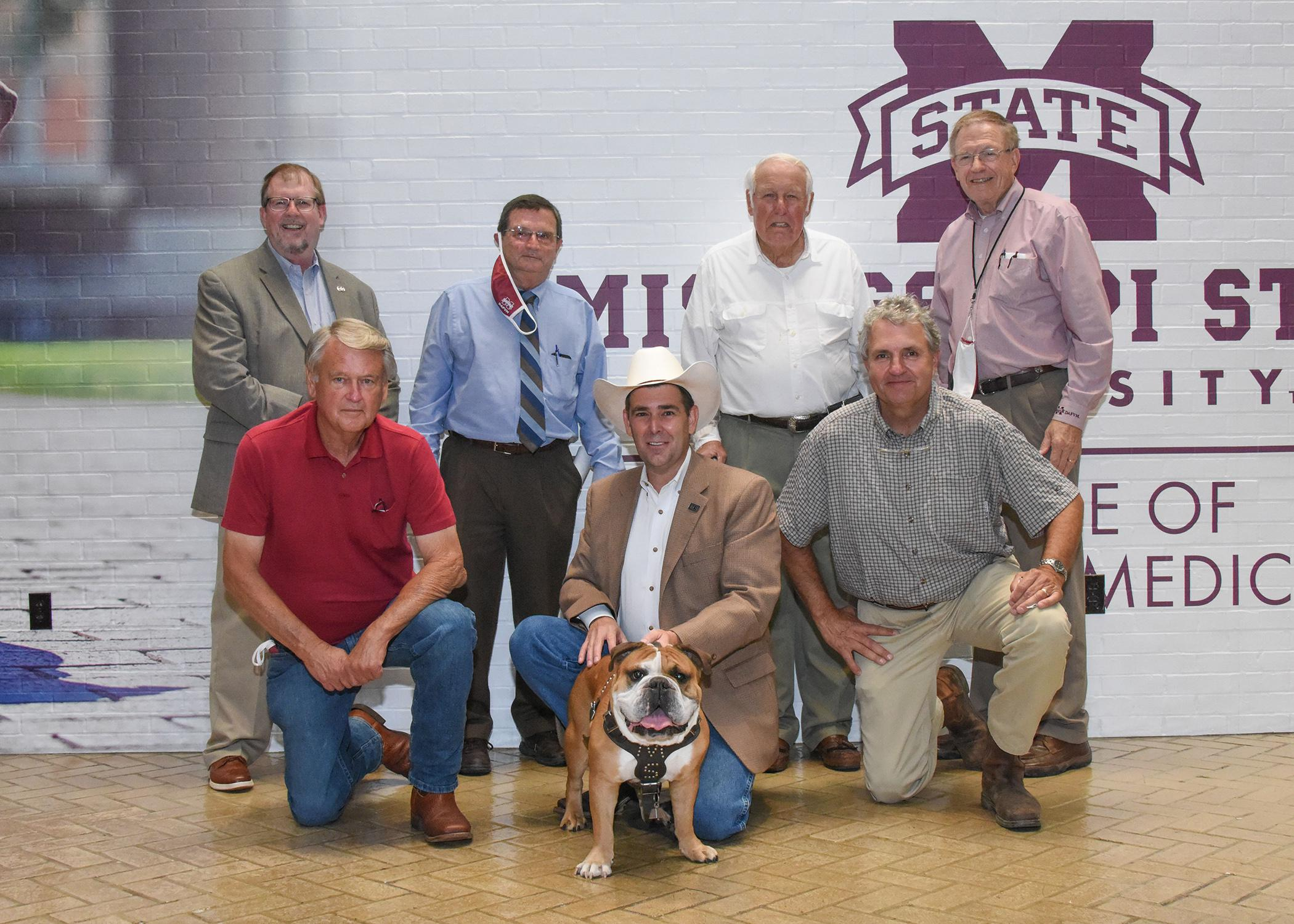 Seven men stand or kneel indoors in two rows, holding a bulldog in the center of the group.