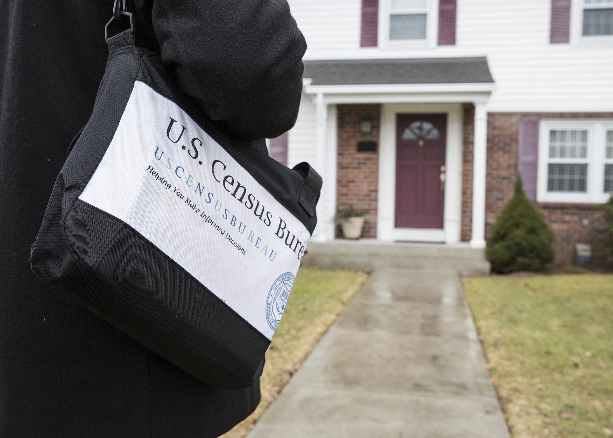 A person carrying a black bag marked with census information approaches the front door of a house.