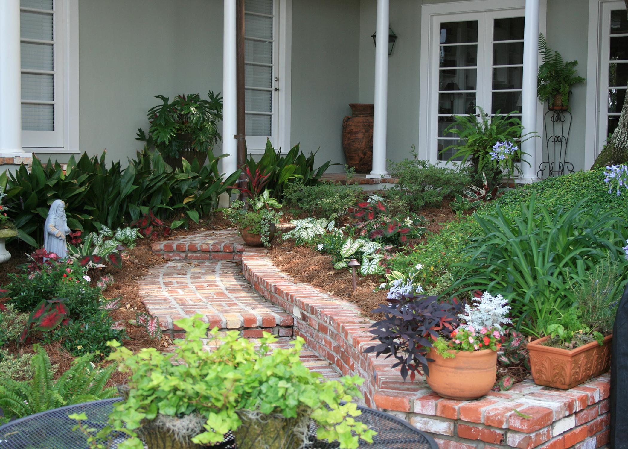 A curving brick walkway lined with plants leads up to a porch.